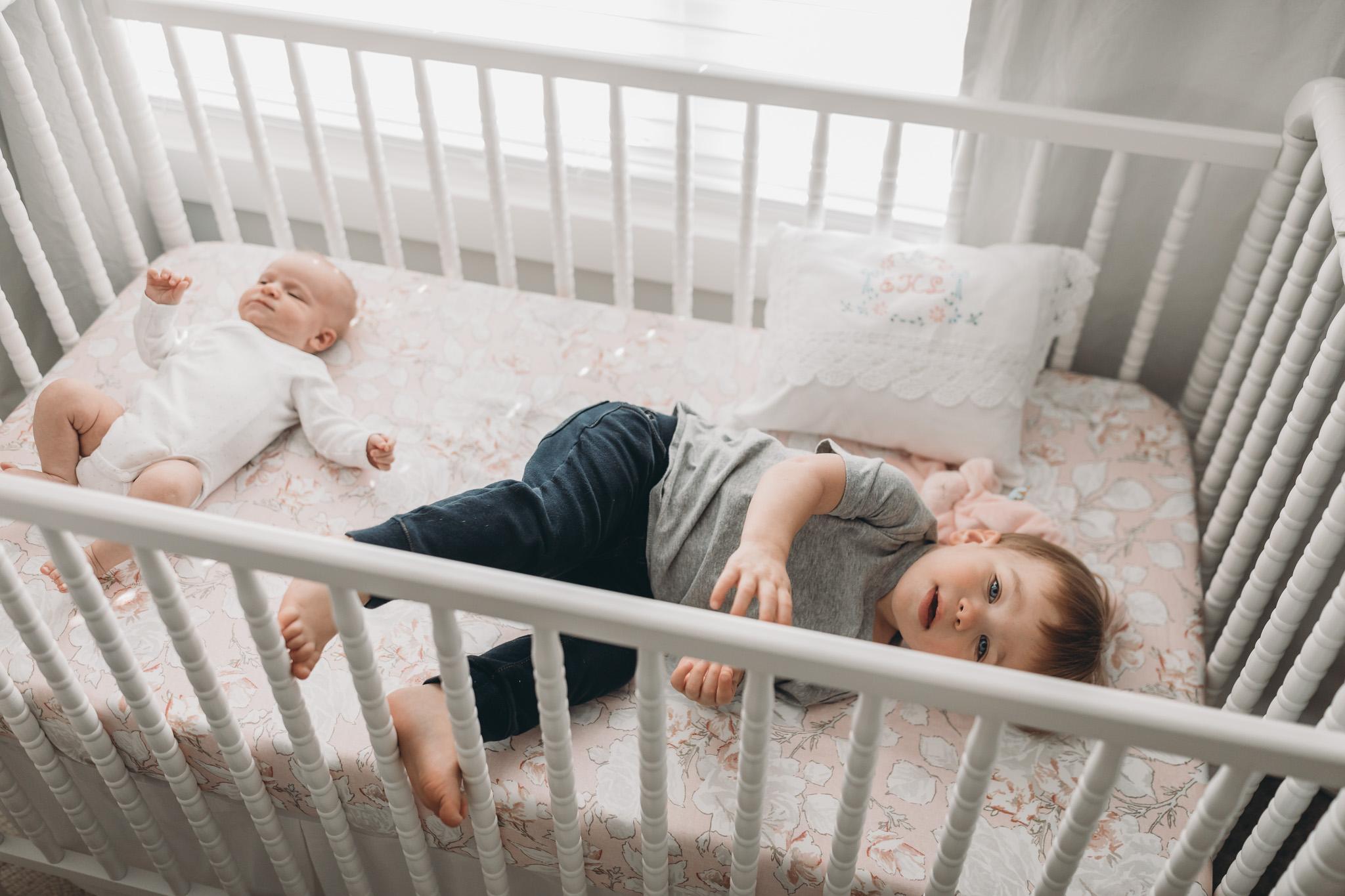 Siblings Laying in Crib