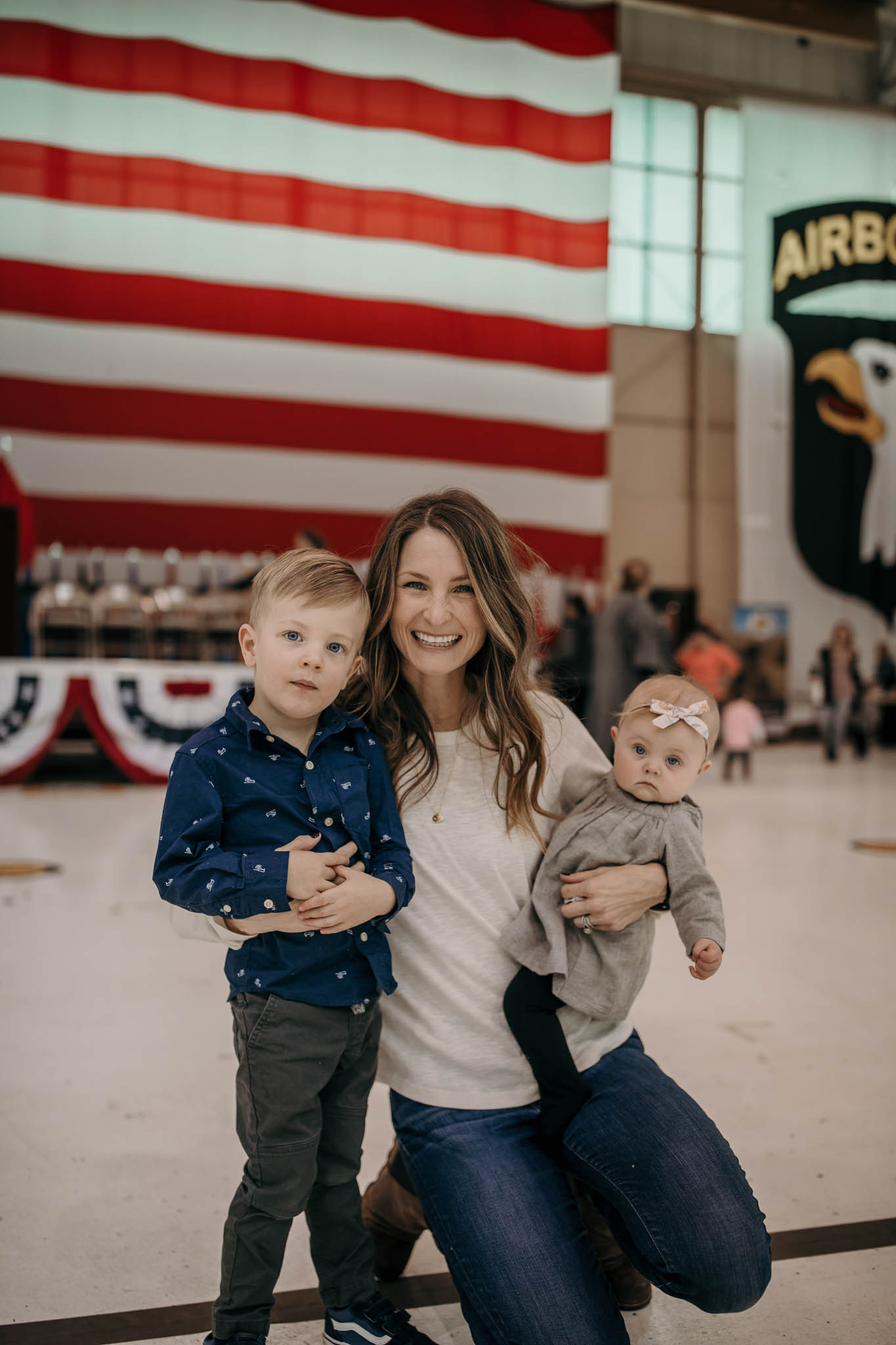 Army Wife Standing with Children infron of Flag