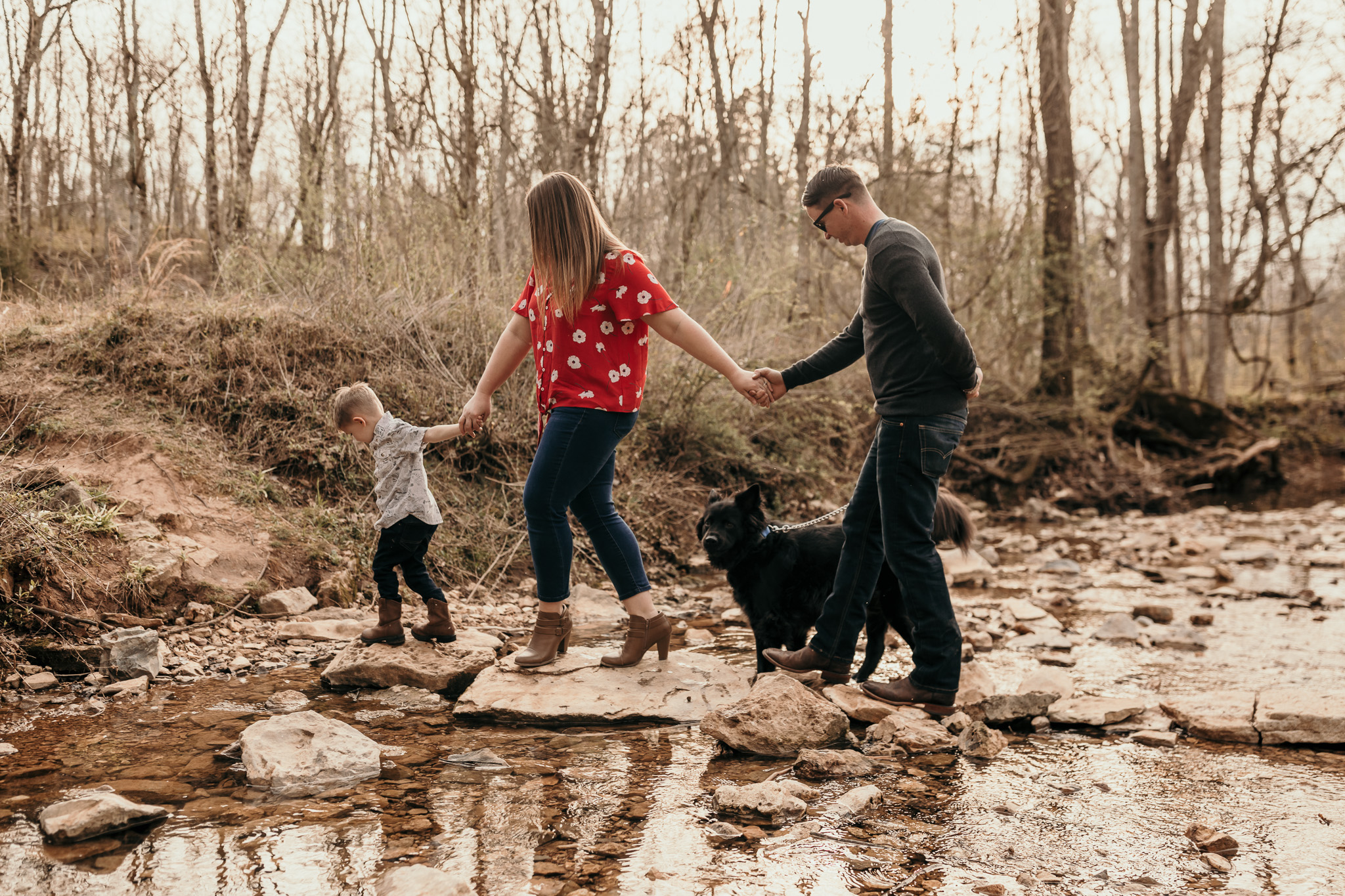 Family Walking Across Creek
