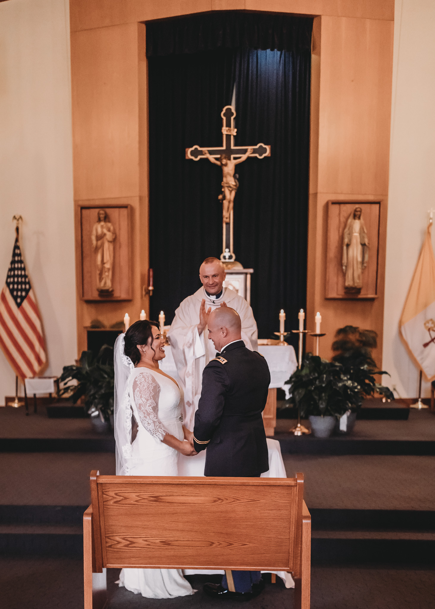 Bride and Groom Standing Infront of Cross