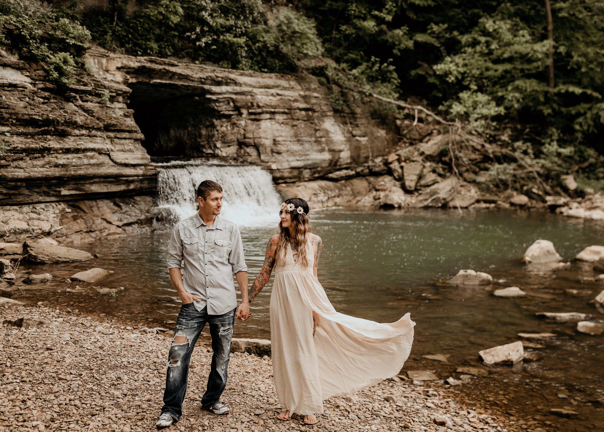 Couple holding hands infront of waterfall