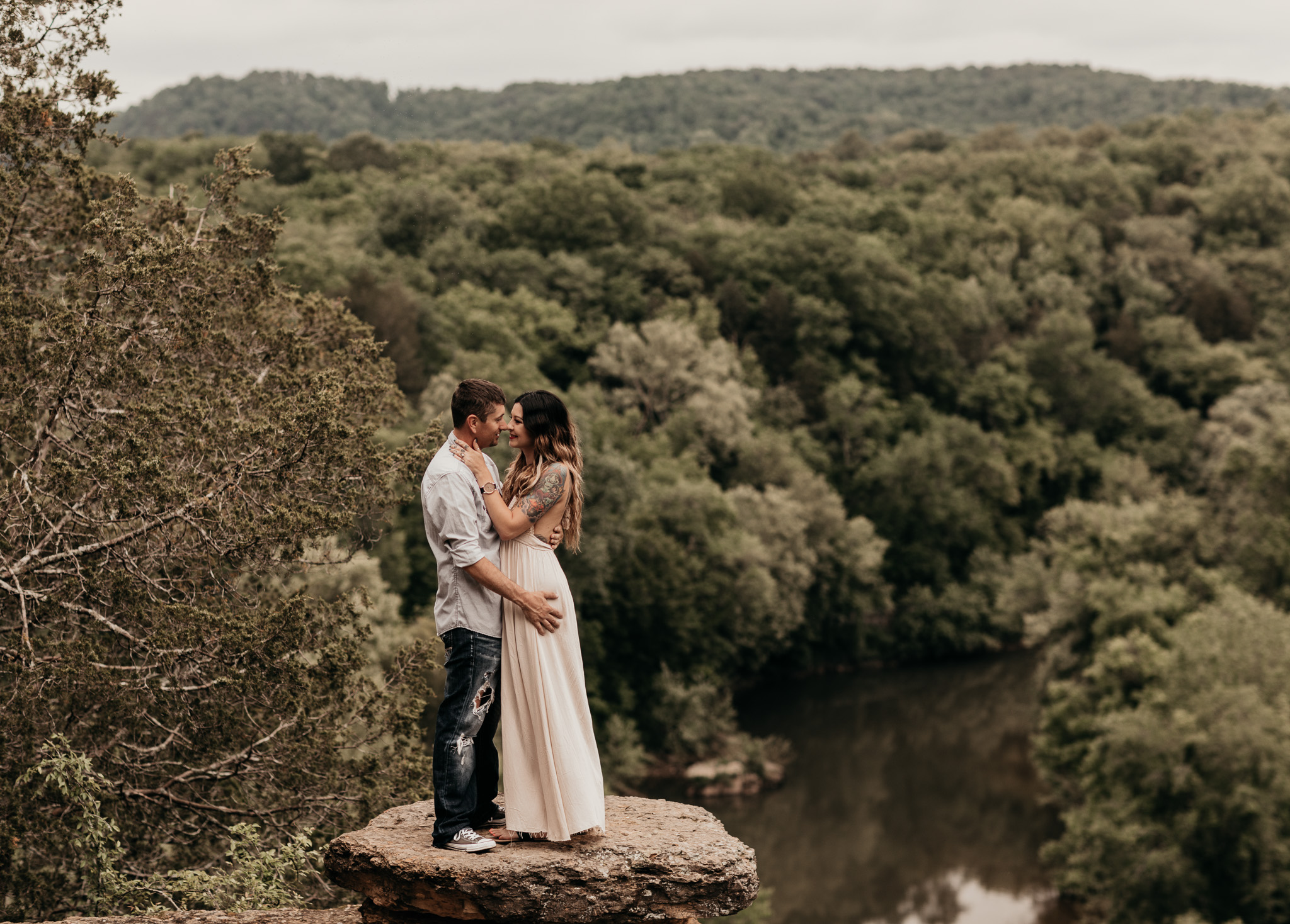 Couple kissing as they stand on a rock