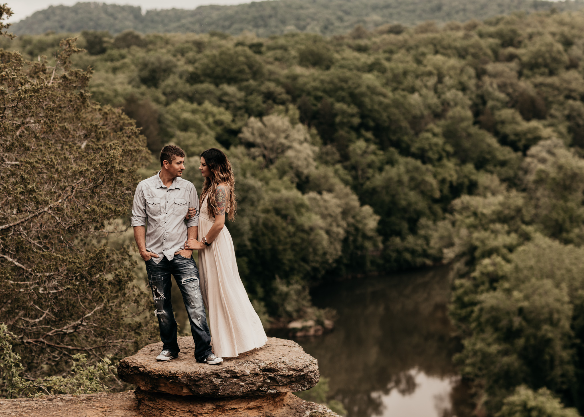 Couple standing on rock looking at each other