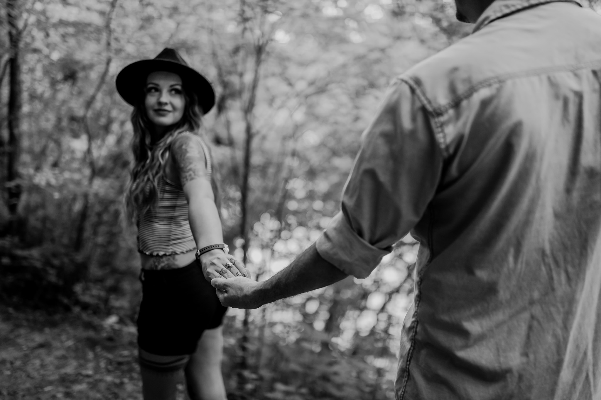 Black and white photo of girl handing hold her man's hand
