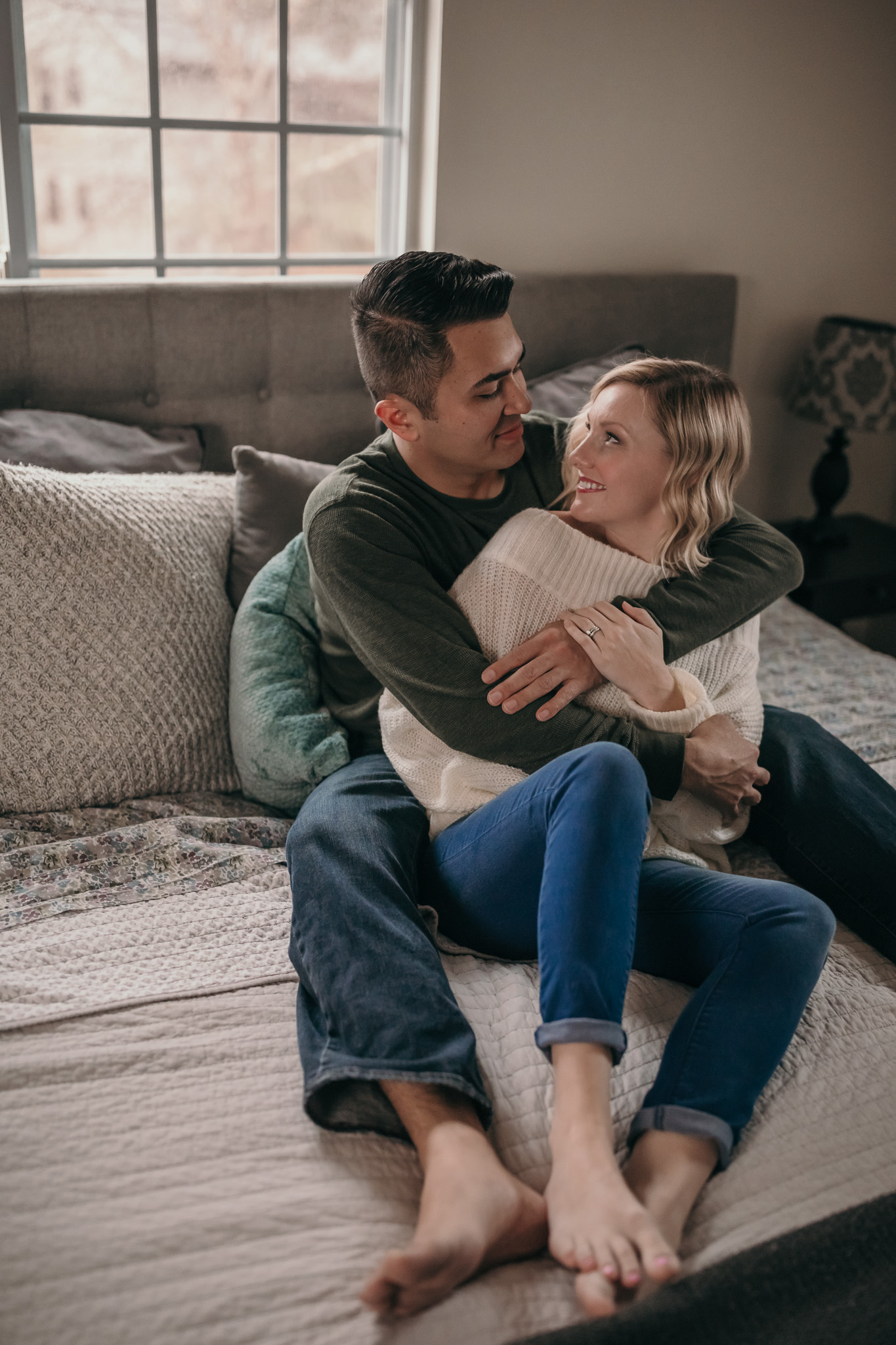 Couple embracing sitting on bed