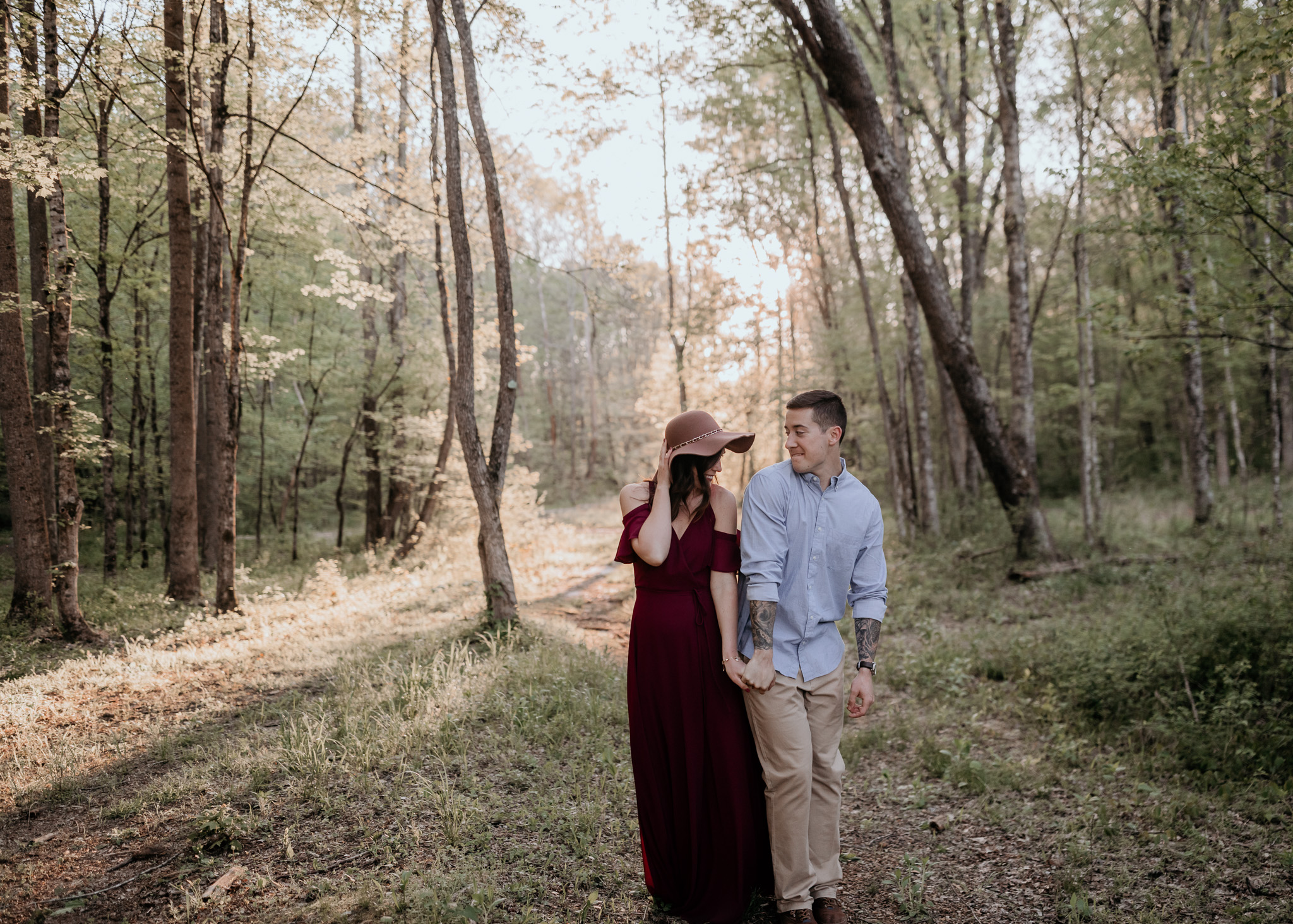 Engagement photo of couple with woman in maxi dress and hat