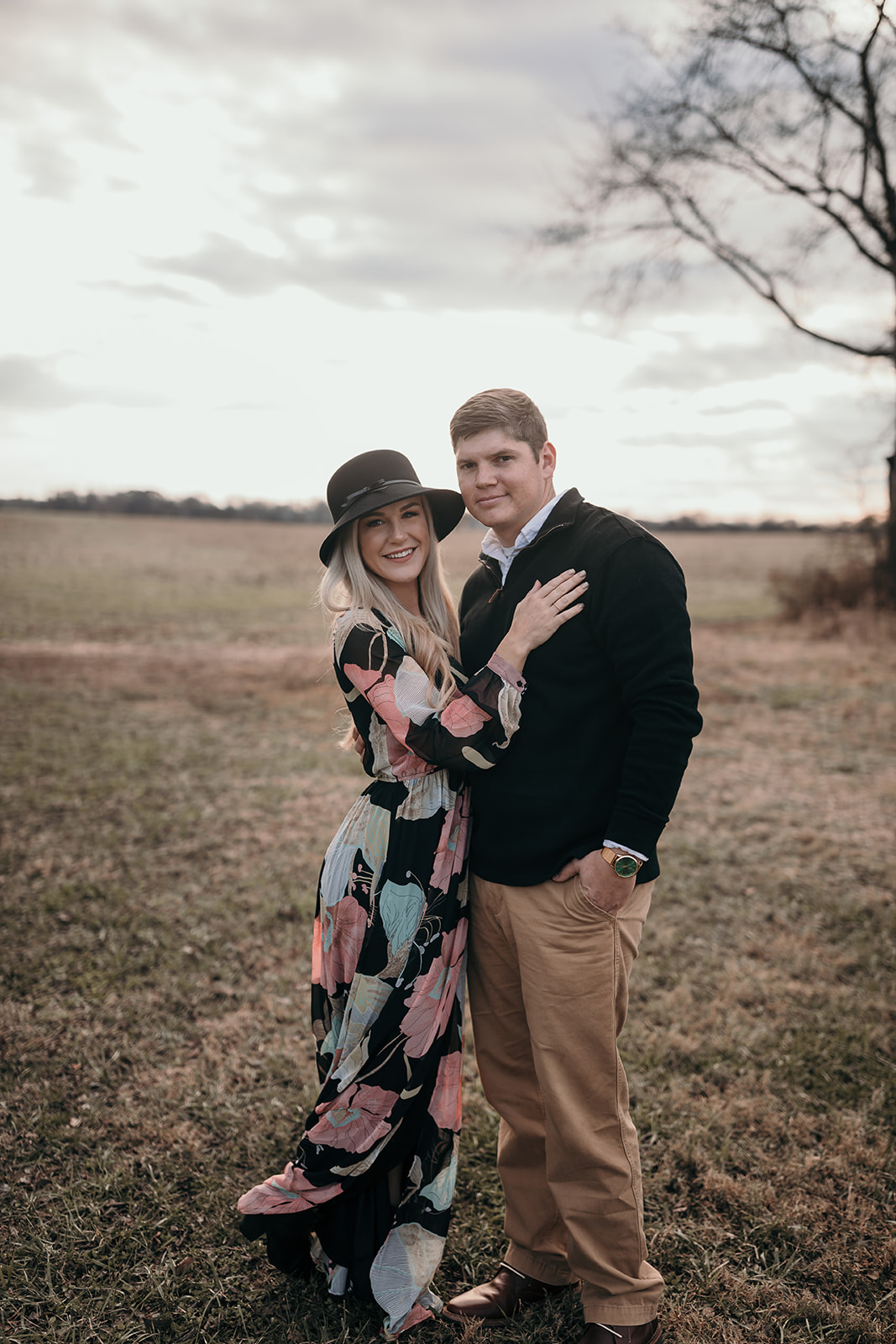 Couple standing together in a field smiling