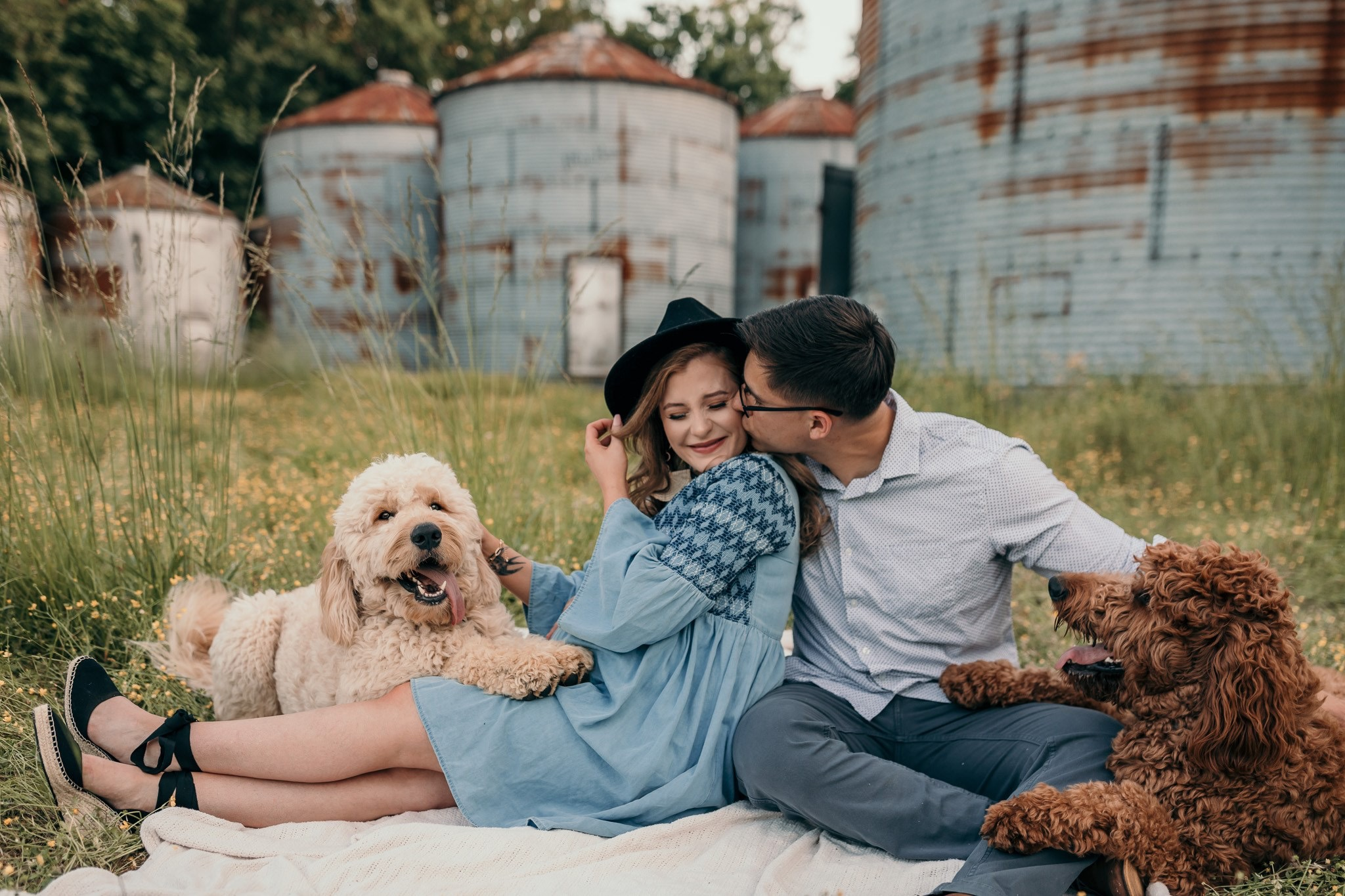 Couple sitting on a blanket together with their two goldendoodles