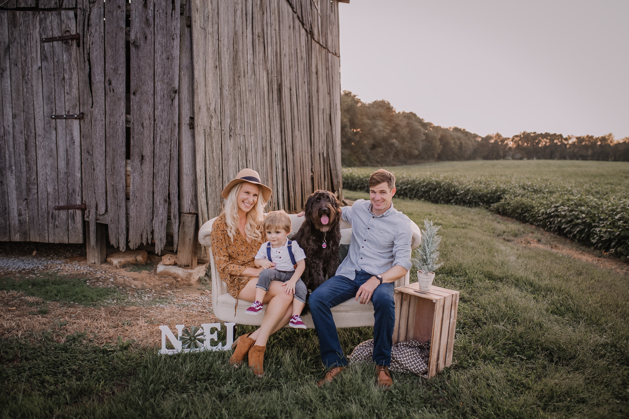 Family sitting on sofa in front of barn with their pup