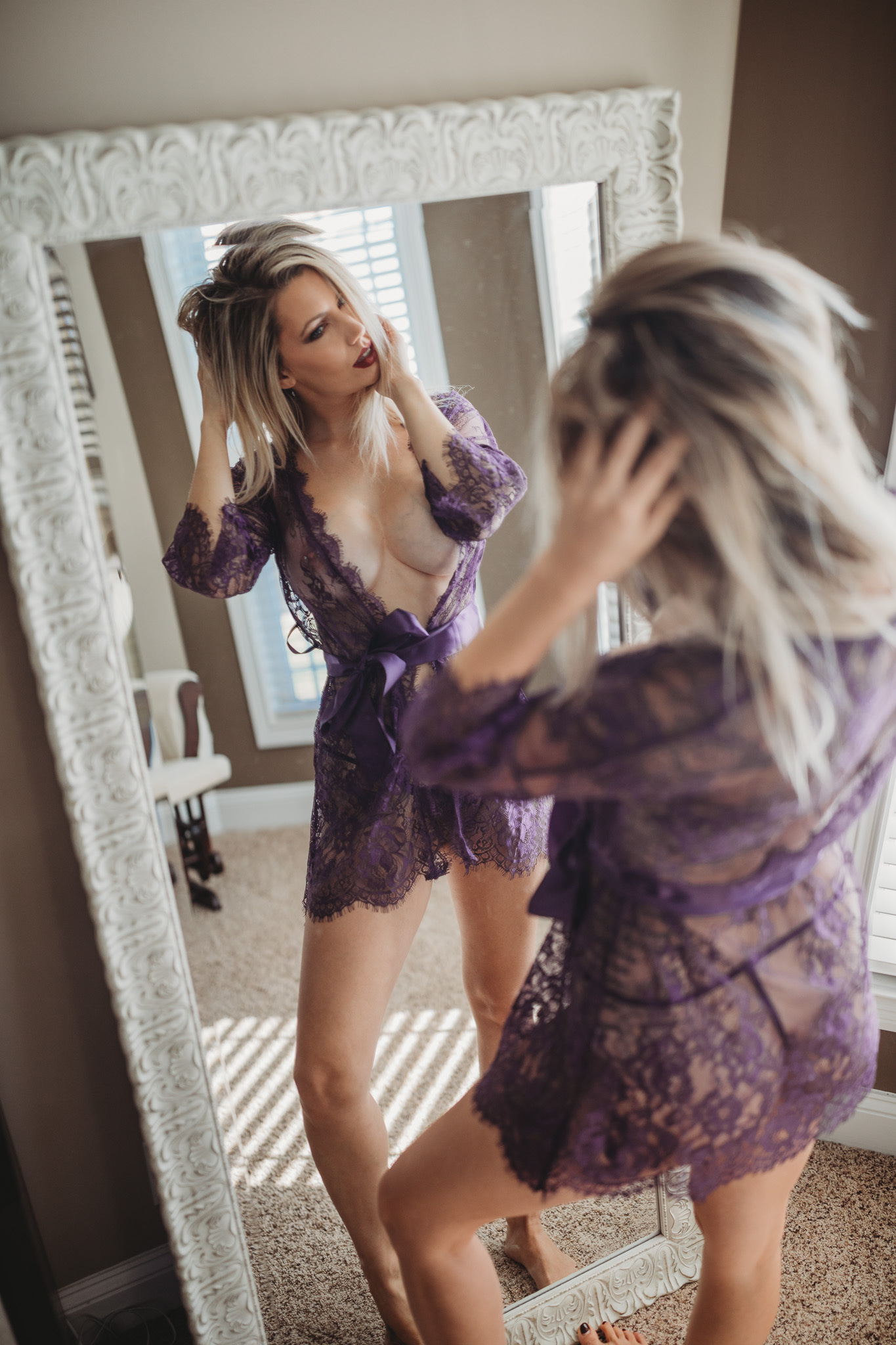 Girl in lace robe looking in the mirror