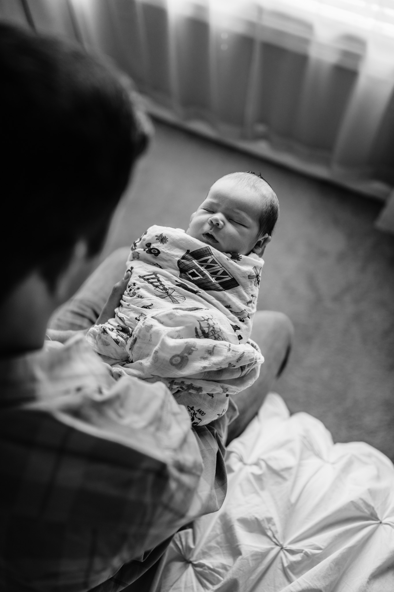 black and white of dad with newborn