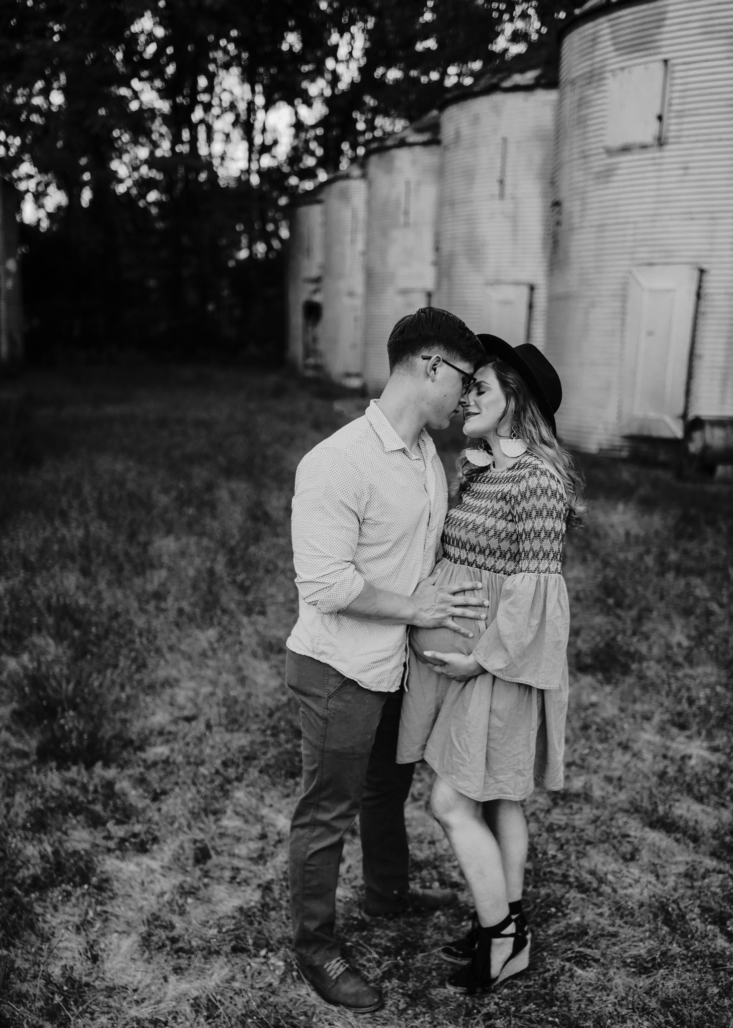 black and white maternity photo of couple standing and embracing