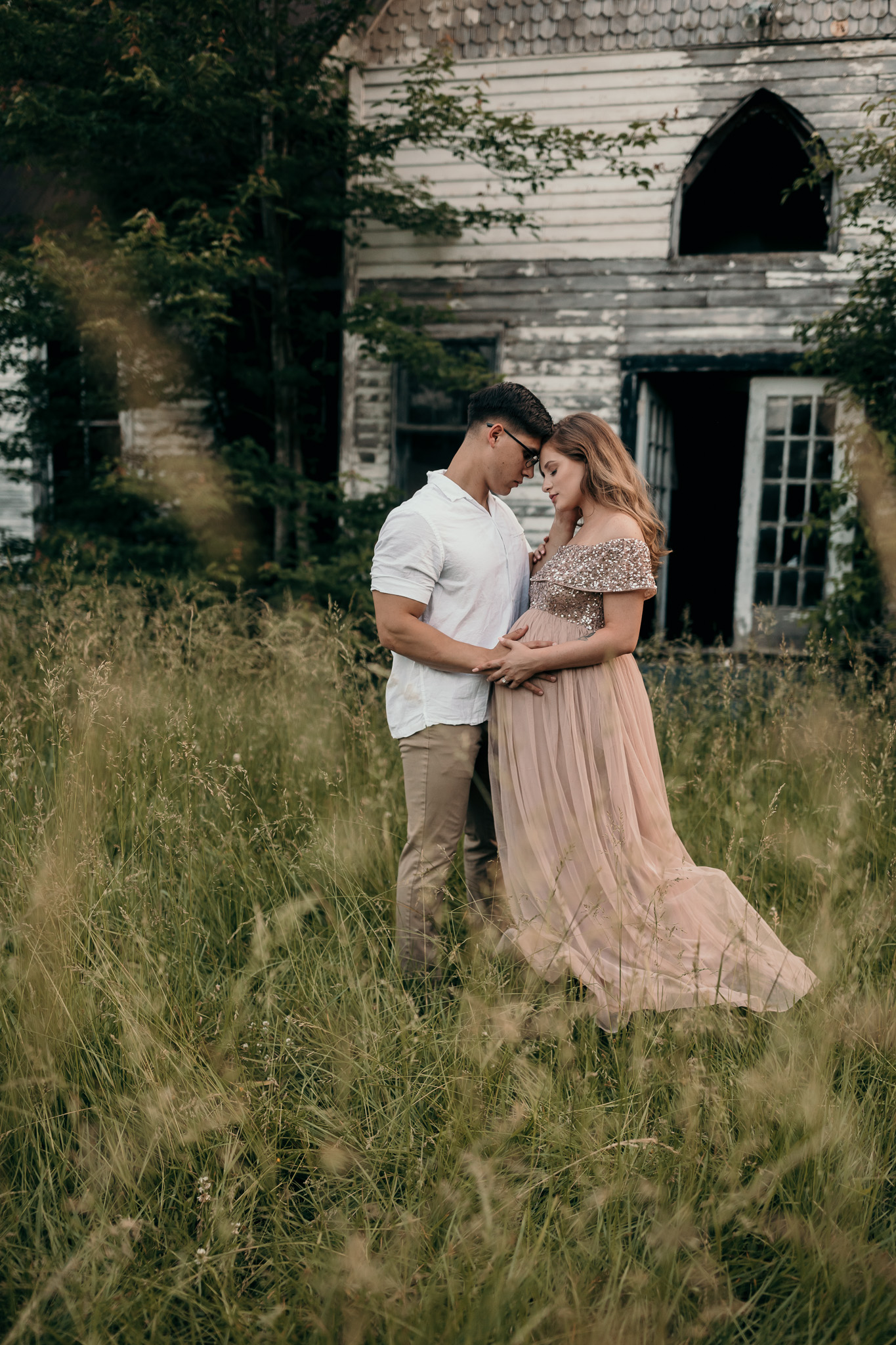 man and woman embracing for maternity photos