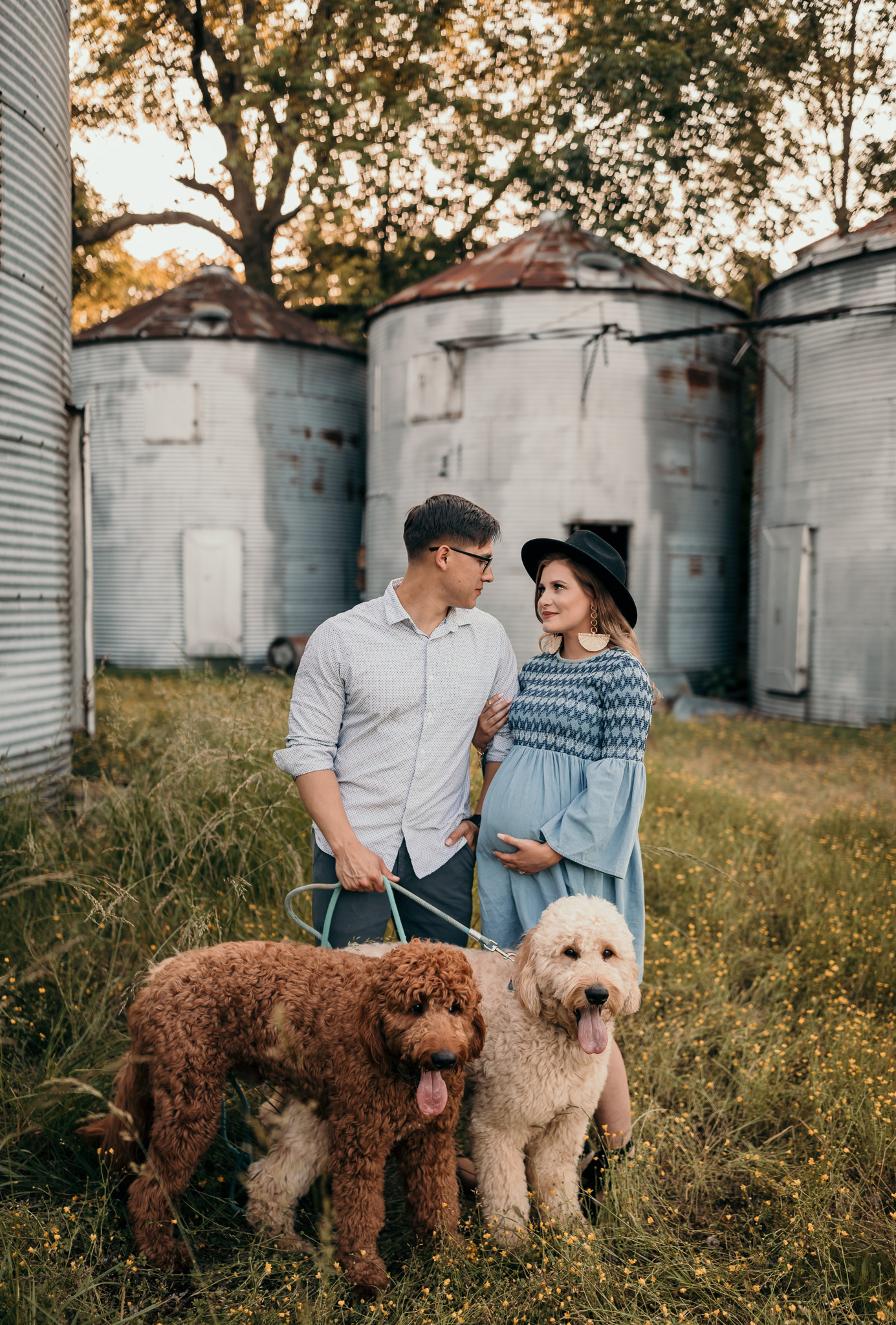 husband and wife with goldendoodle dogs