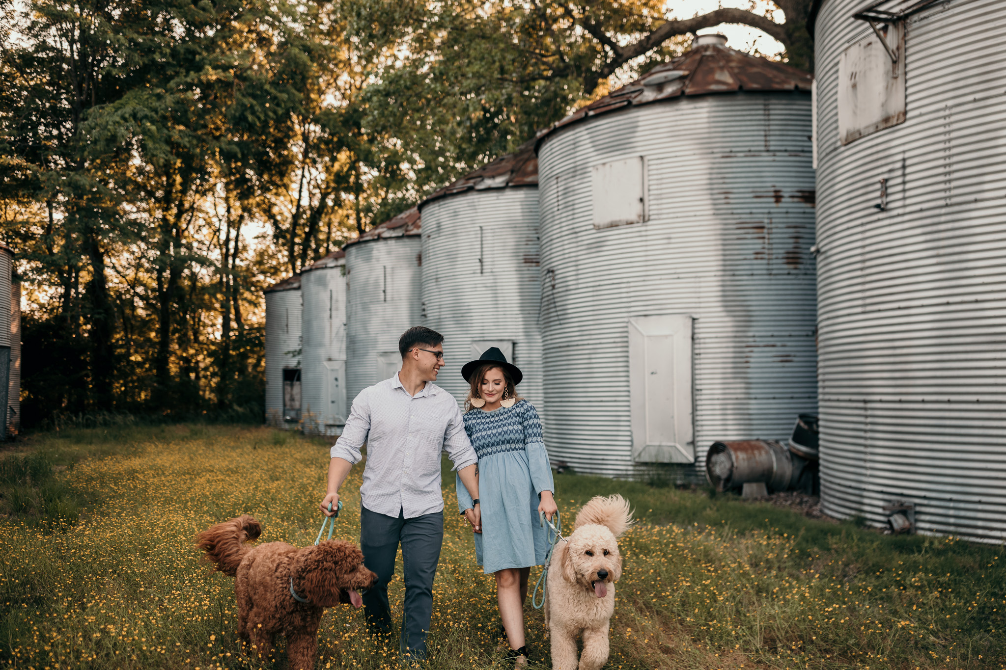 couple with two goldendoodle dogs walking