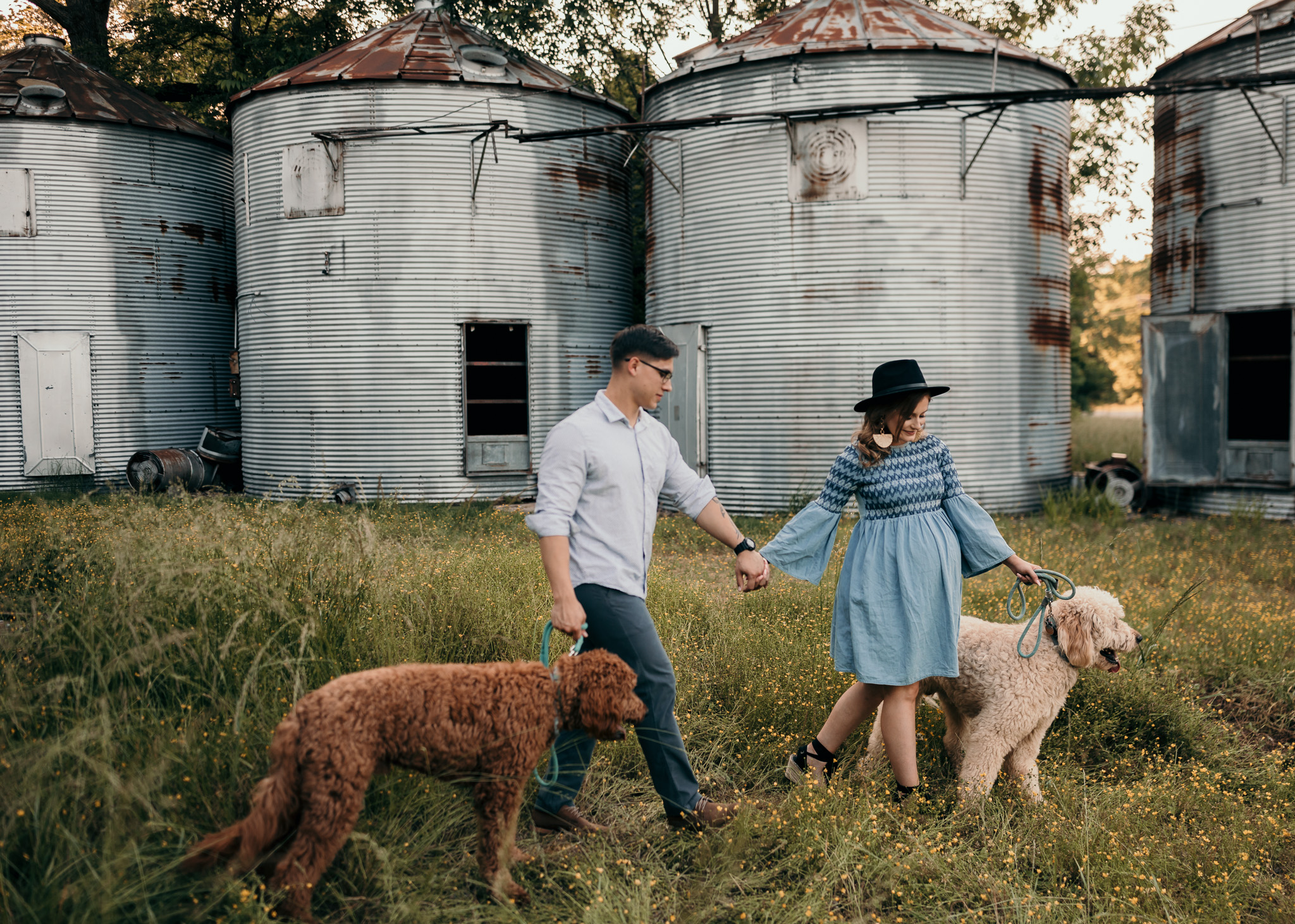 couple with two goldendoodle dogs in maternity photos