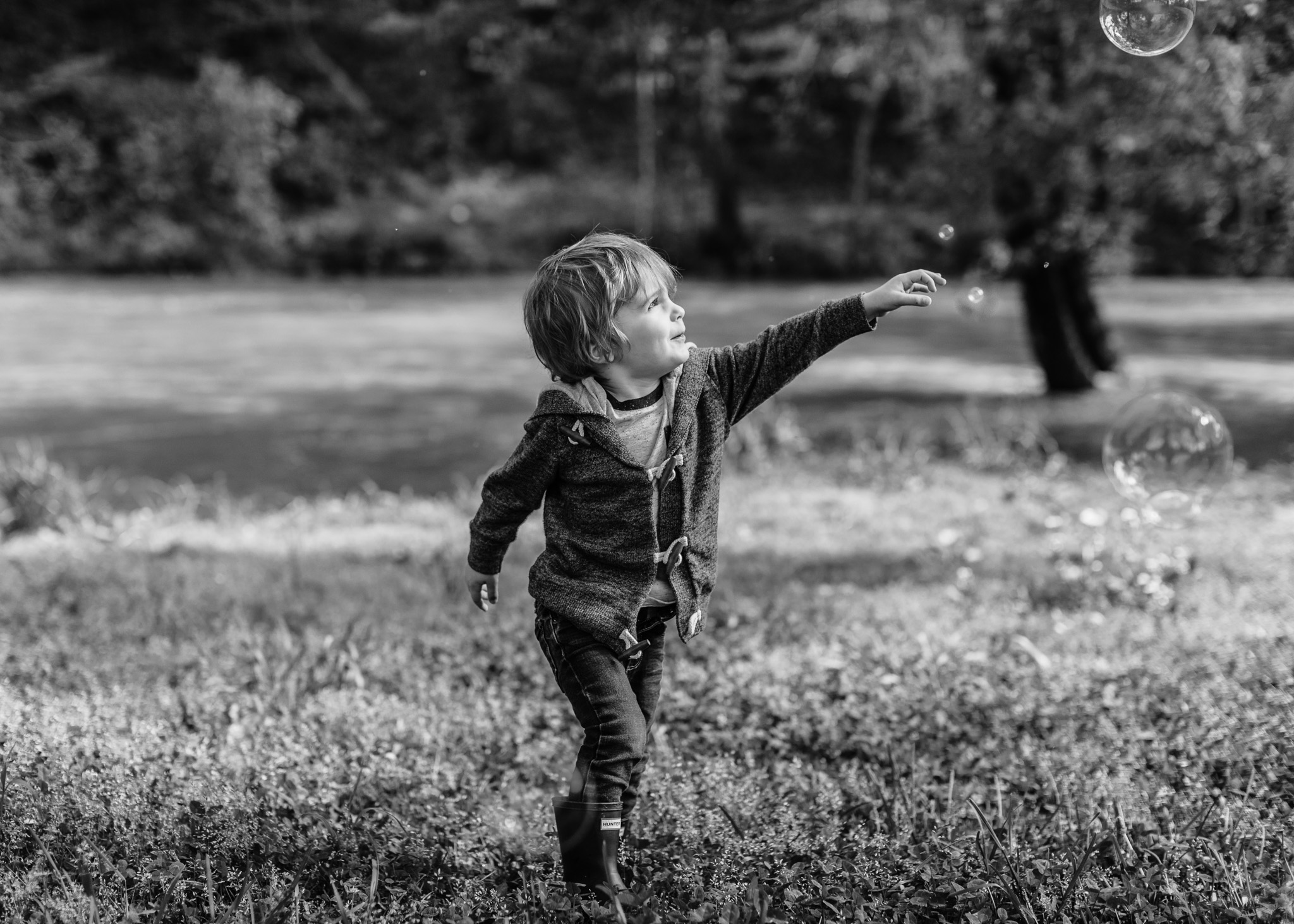 boy playing with bubbles in black and white