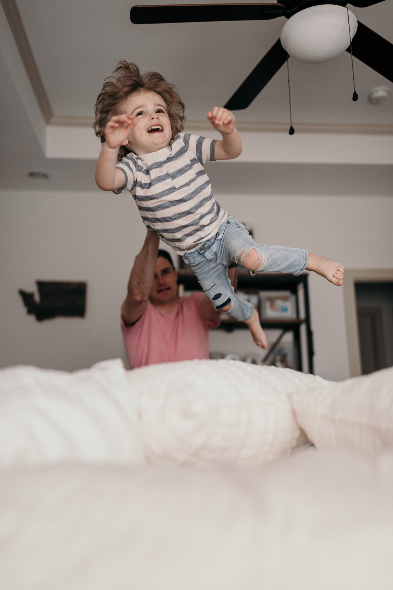 dad throwing son on bed