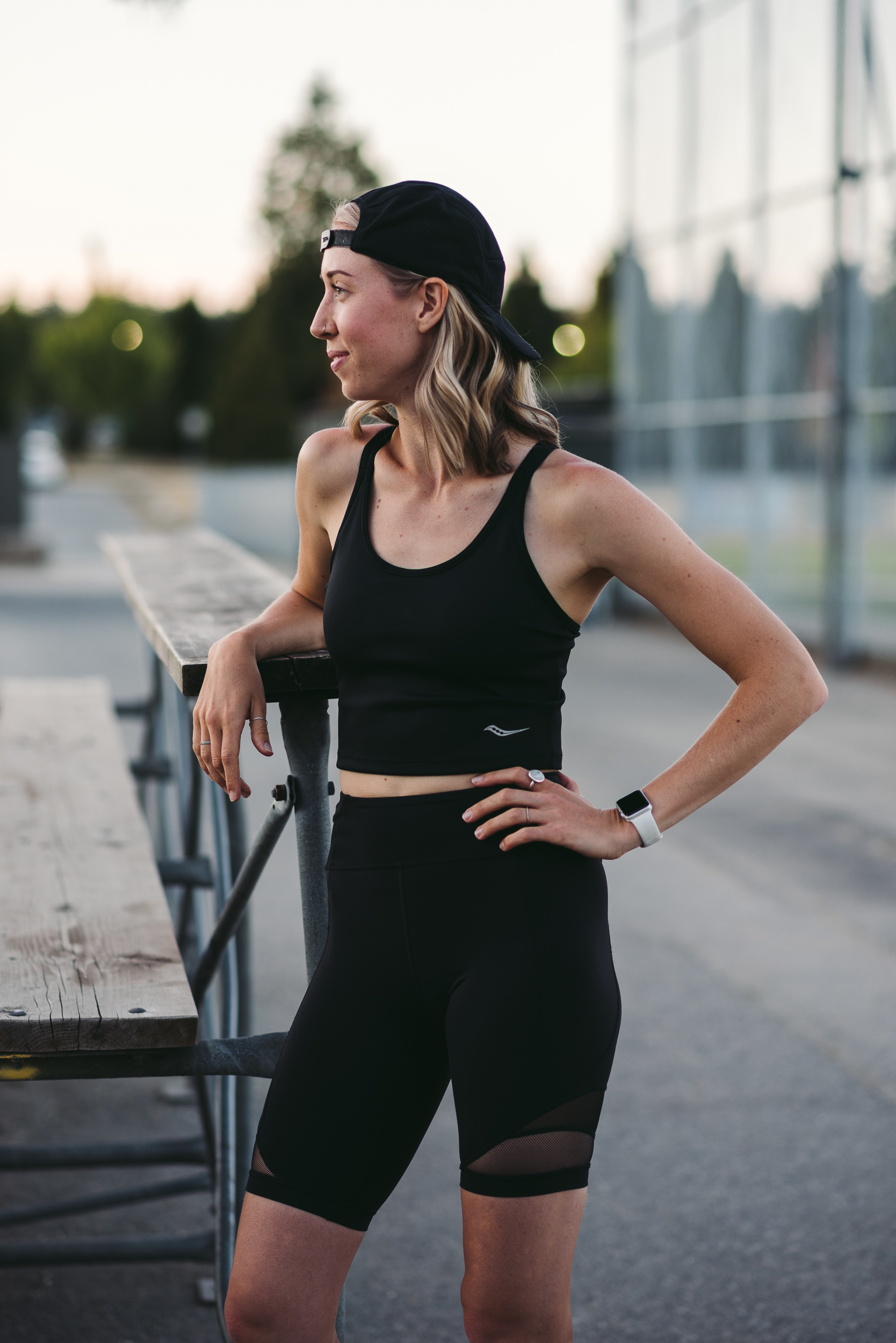 Mint Club Athletics founder, Sara, leaning again stadium benches and smiling