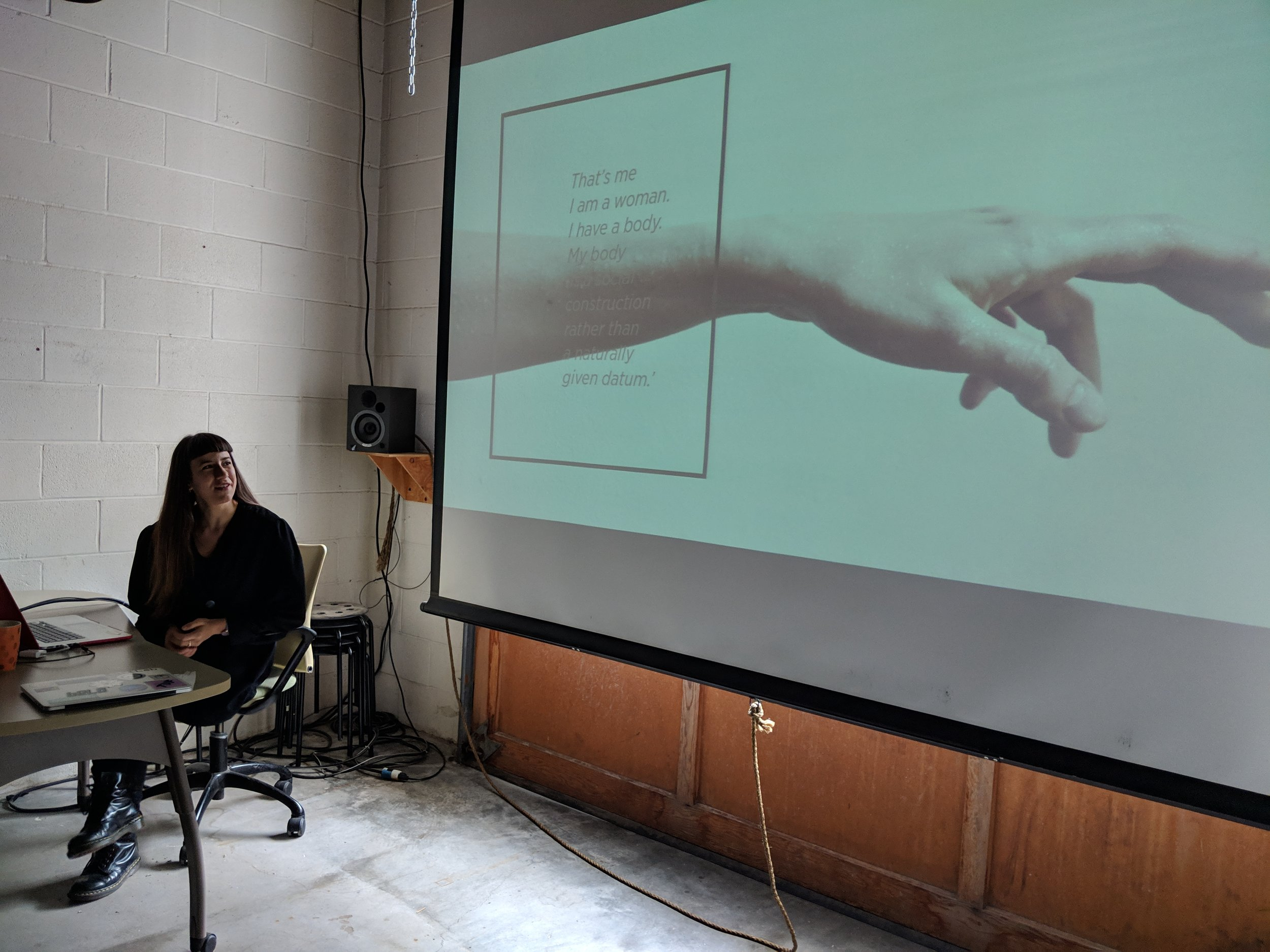 "Giulia Tomasello introducing her work to the DXARTS 490 students with this quote from Simone de Beauvoir: ""That's me. I am a woman. My body is a social construction rather than a naturally given datum""."