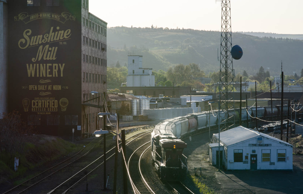 Sunshine Mill Winery in The Dalles, Ore., lies just on the other side of the overpass from the AmeriTies West facility, where railroad ties treated with creosote off-gas in the yard while awaiting transport. The winery holds events in their outdoor amphitheater including movie nights in the summer.