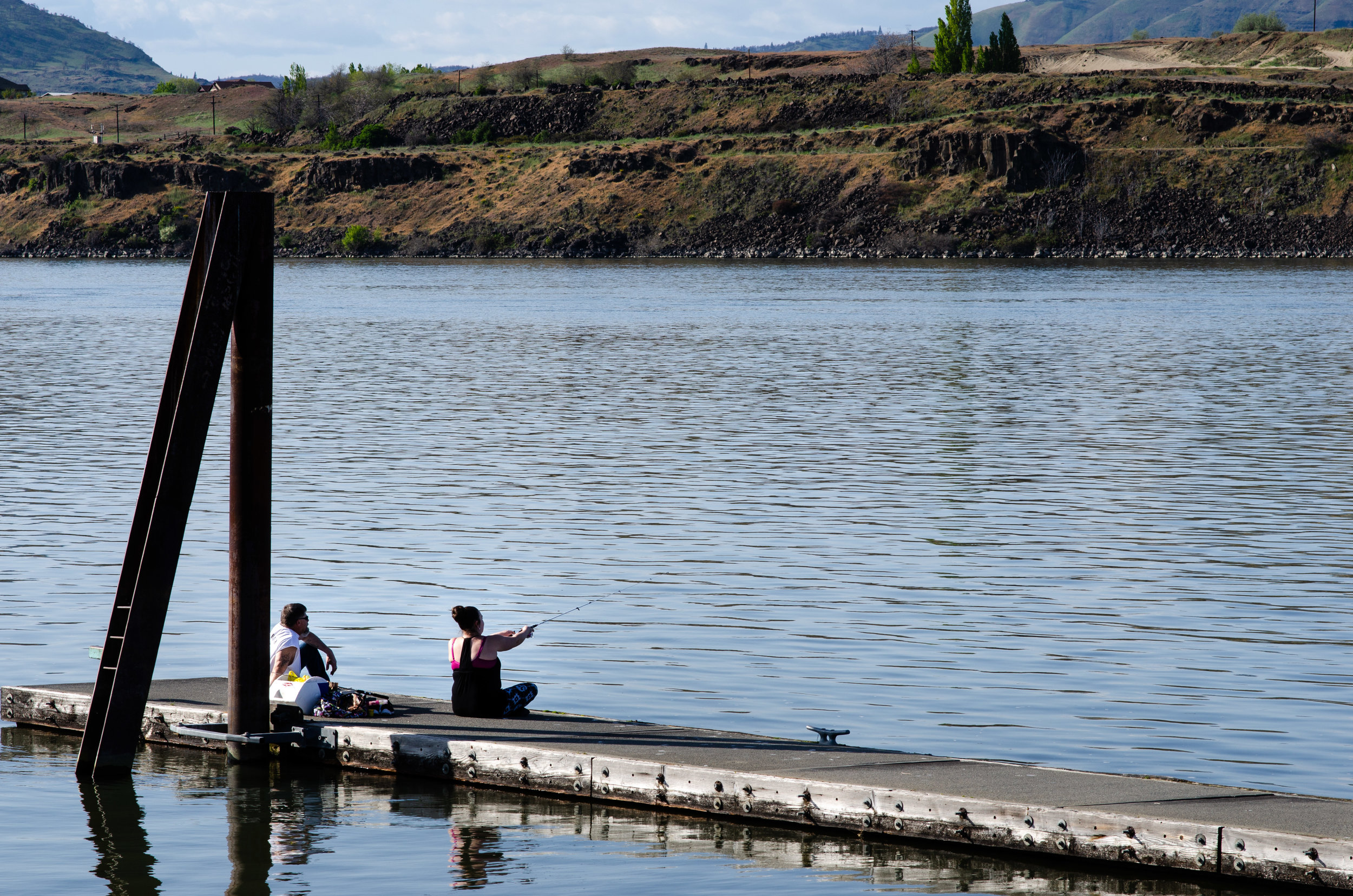 People fishing off the dock at Riverfront Park in The Dalles, Ore. Soil in the Columbia River near the dock is contaminated by pollution from a creosote plant located on shore. The river is home to salmon, steelhead and sturgeon.