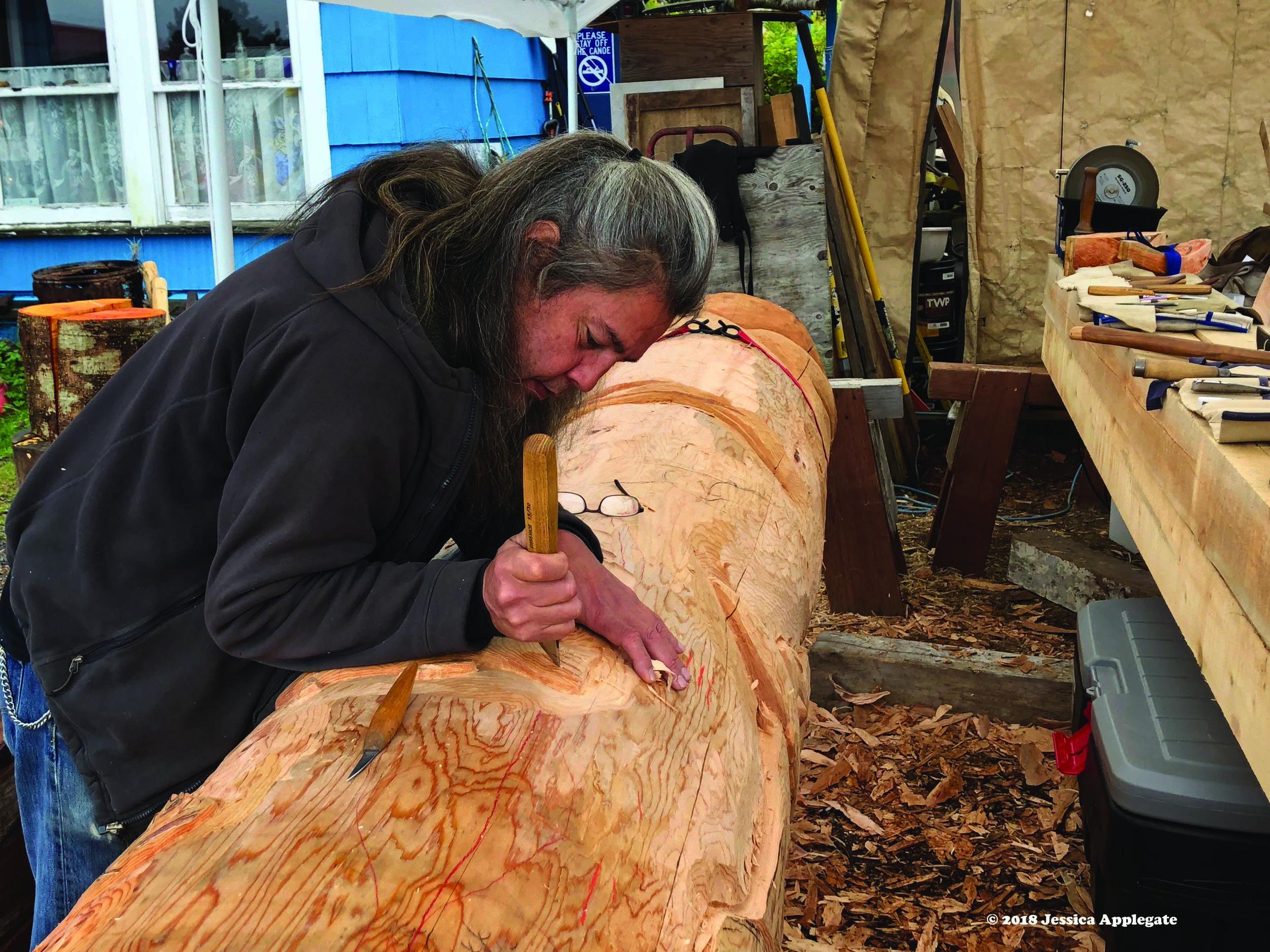 Tommy Joseph, a Tlingit artist in Sitka, carves a totem pole out of an Alaska yellow cedar log.