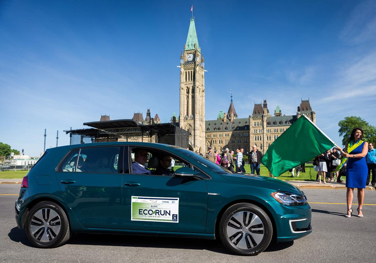 Photos by     AJAC / Feature image:Paula Vieira, Director- Transportation and Alternative Fuels Division, Natural Resources Canada waves the green flag to start the sixth annual AJAC EcoRun.