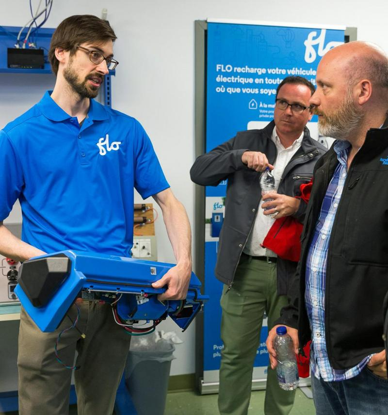 Simon Granger, Head of Content and Communications at FLO shows a Level 2 charger to AJAC journalists at AddEnergie headquarters.