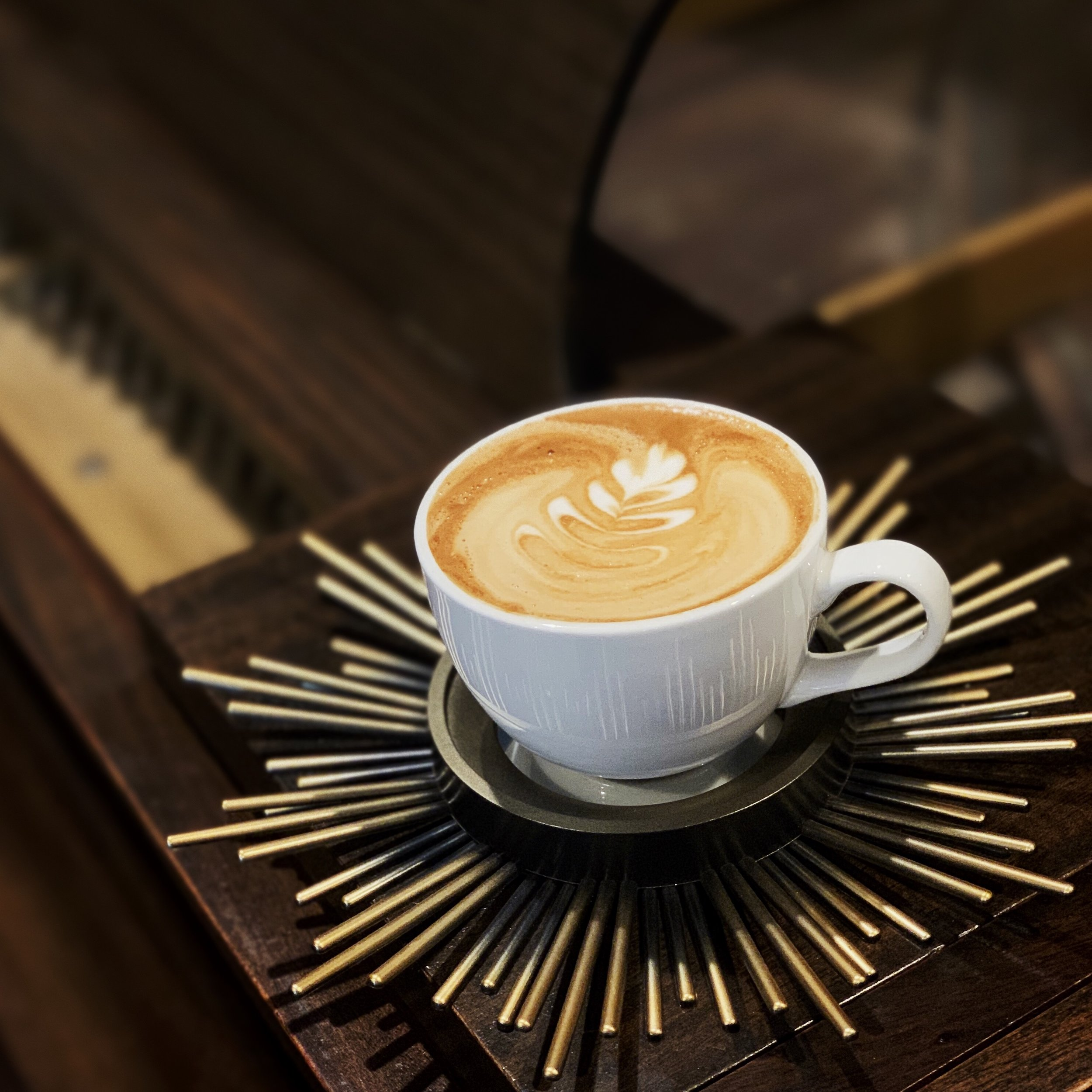 Rosetta Latte Art in a classic white cup in a gold cup holder on top of piano at Americano Coffee Lounge 434 Houston Street Suite 120 Nashville Tennessee 37203.