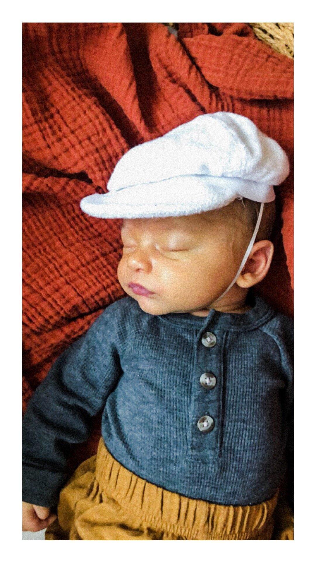 Newborn in a white hat. Photos taken via FaceTime