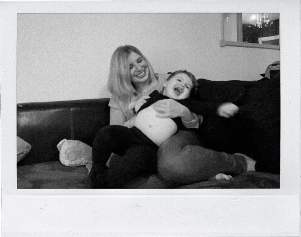 Mother and son laughing on a couch taken through FaceTime