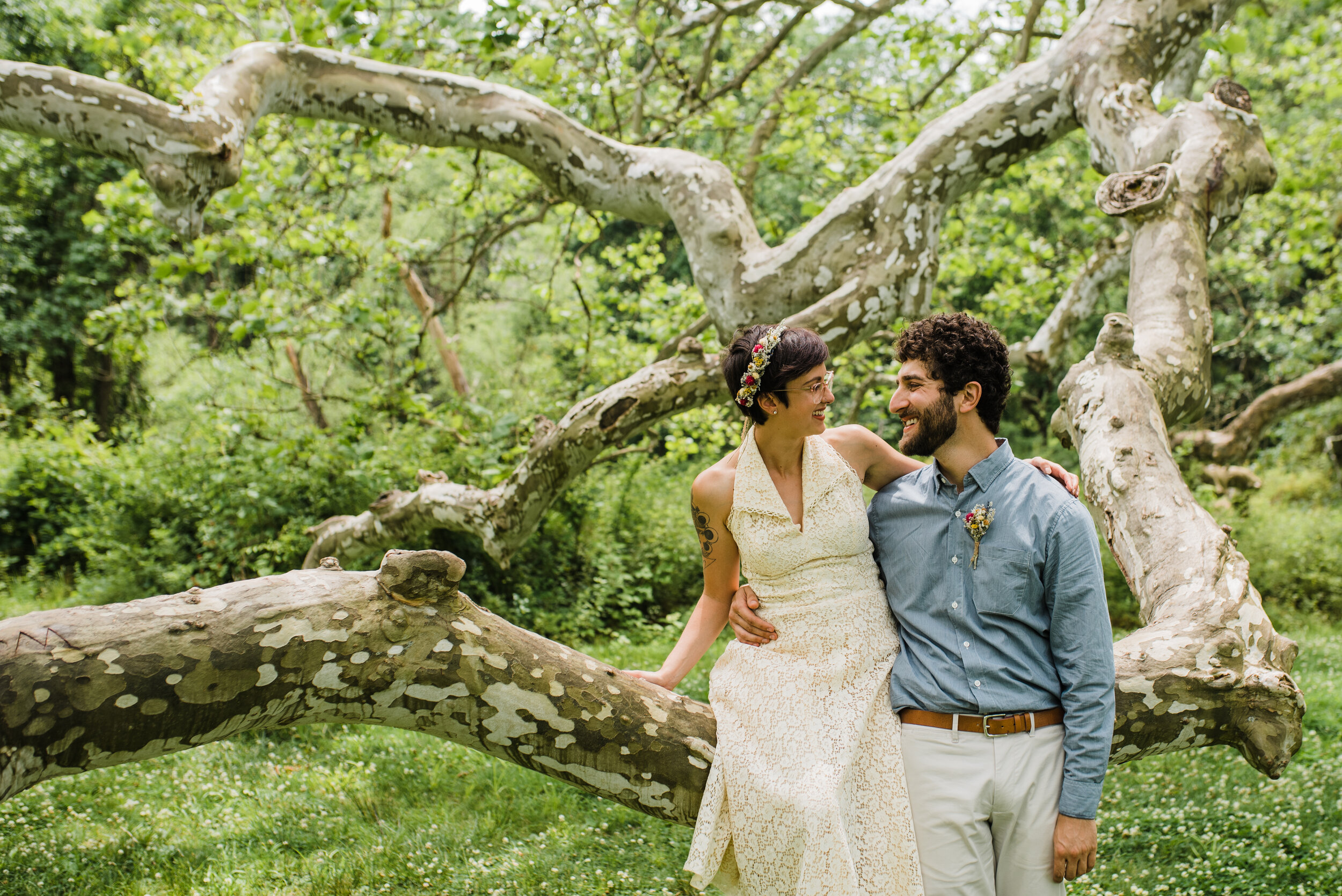 Wedding couple on a large tree. Bride is wearing a vintage inspired dress, flower crown and short hair.