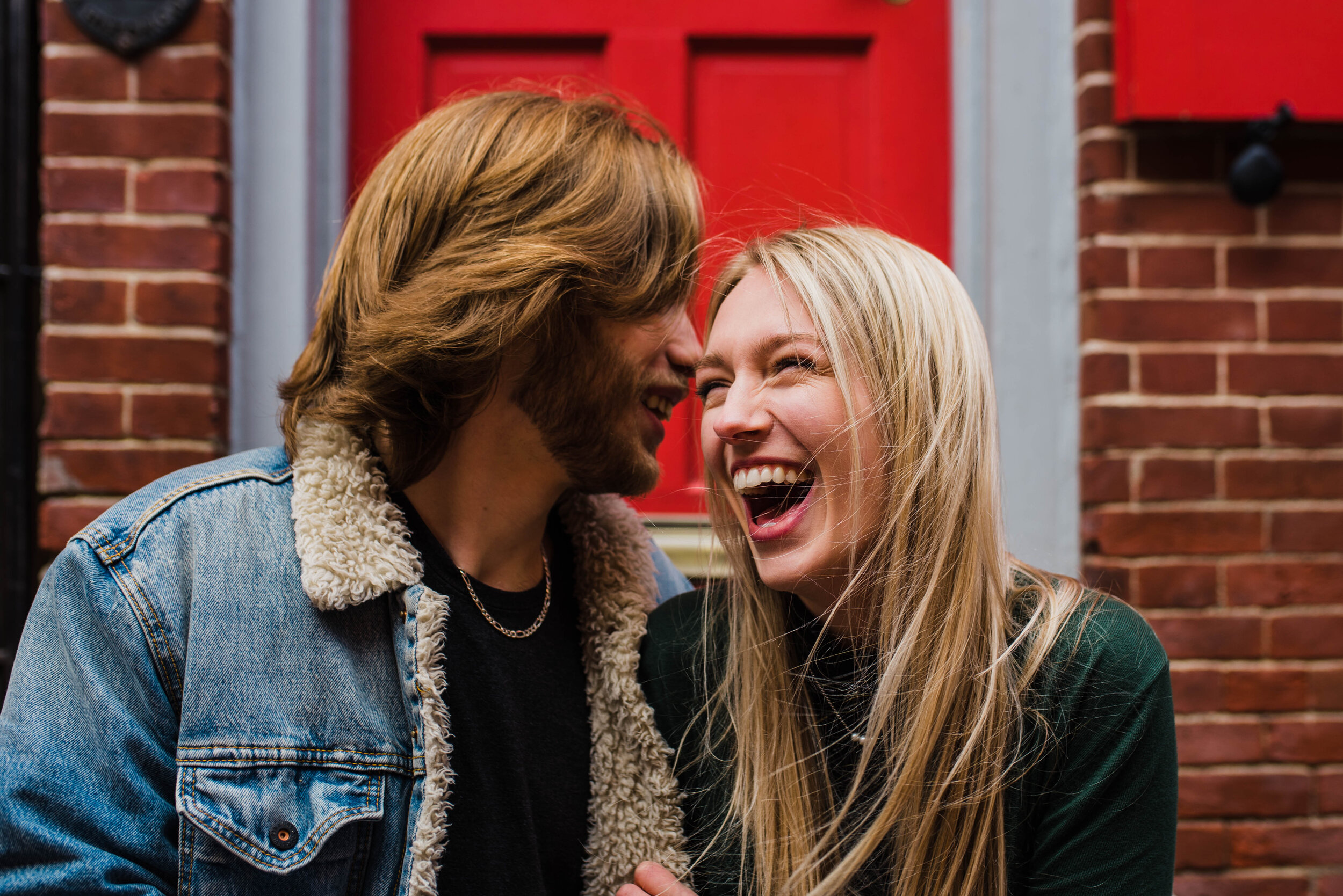 Laughing couple in front of a red door.