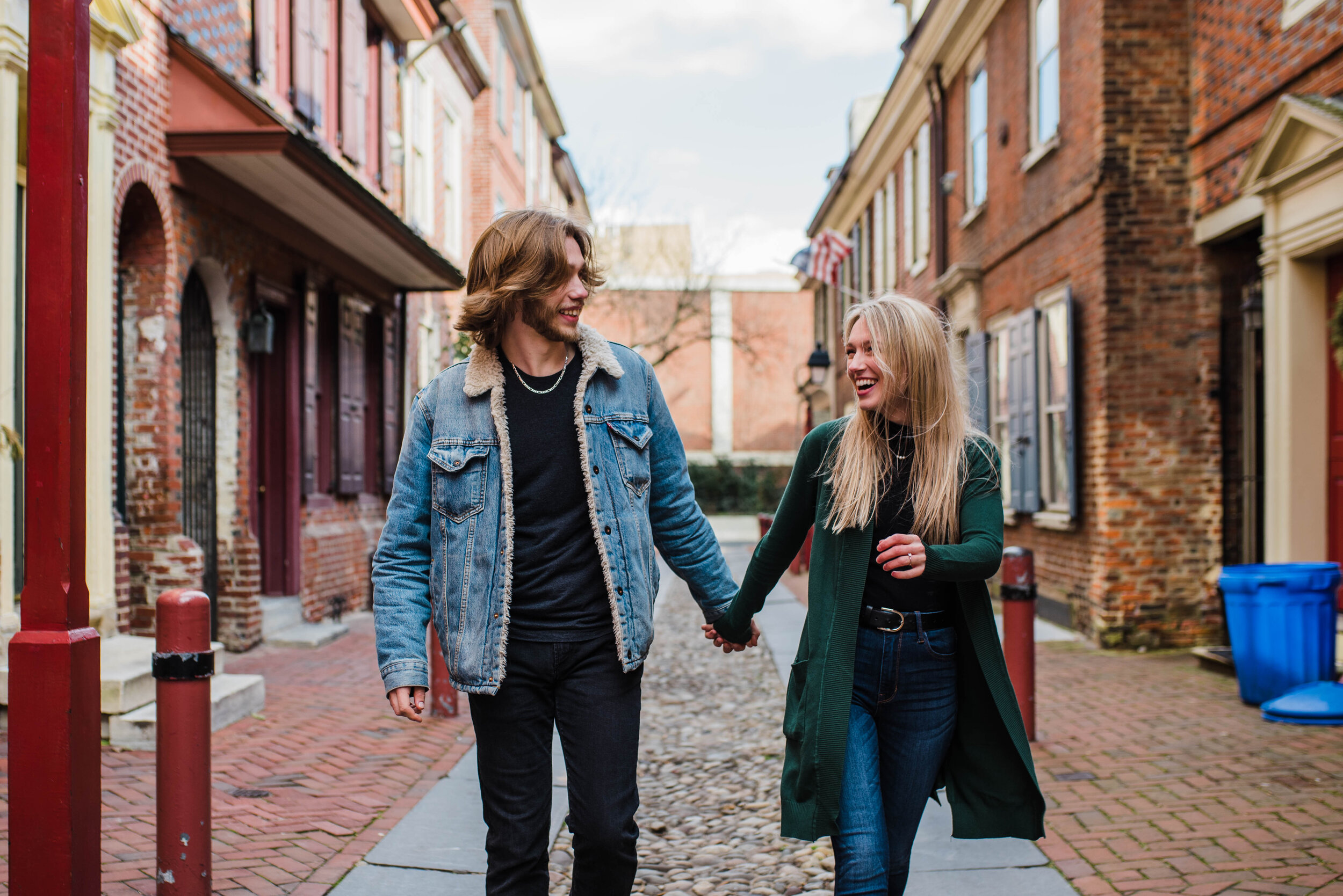 Couple holding hands and walking down a cobblestone road.