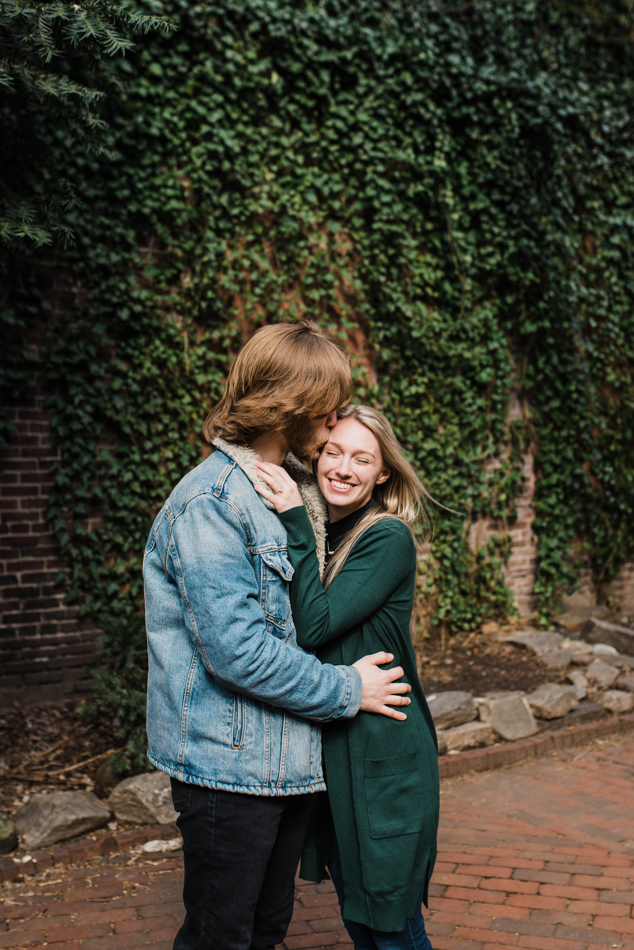 Couple hugging with ivy in the background.