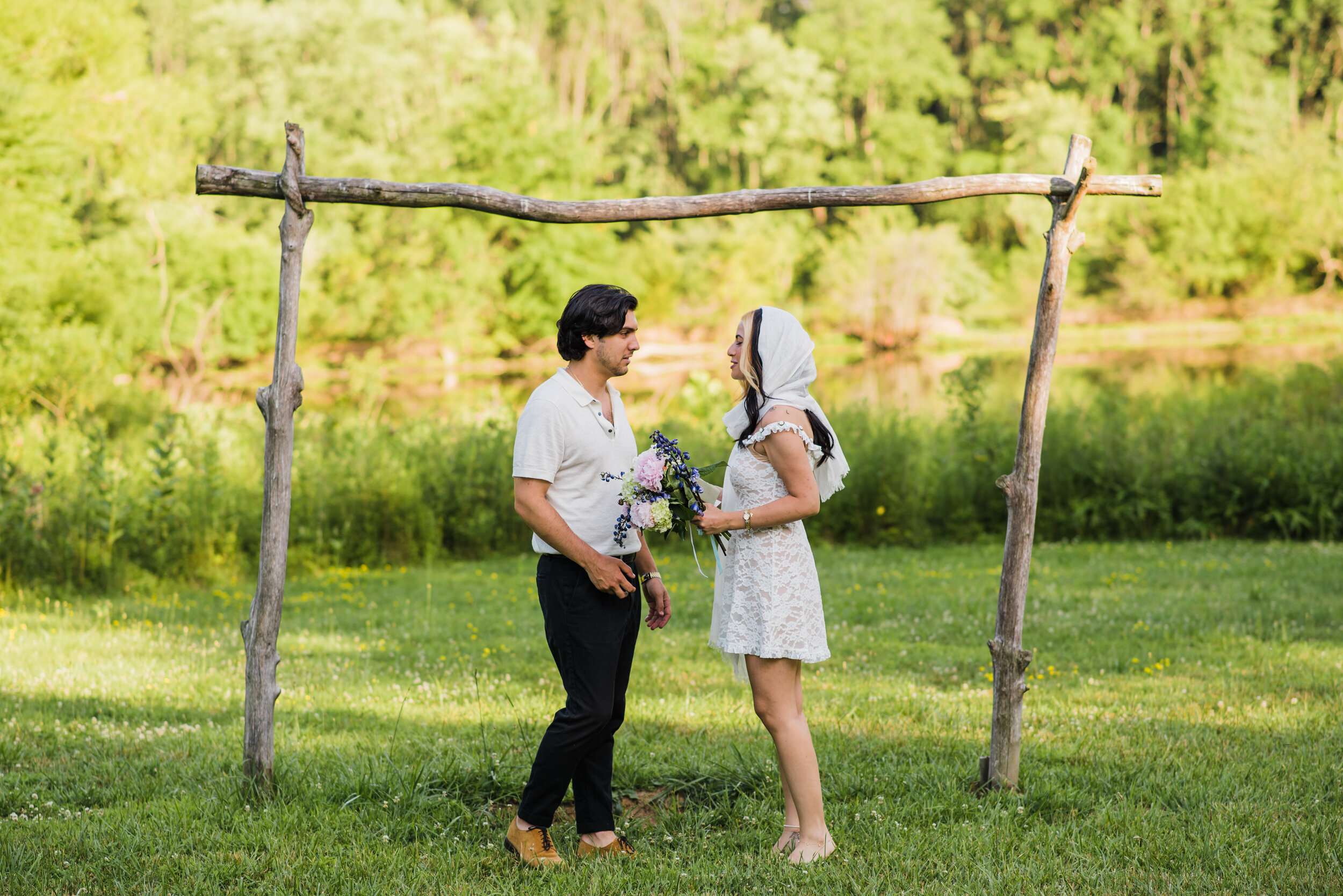 Wedding couple exchanging vows under a rustic arch outdoors.