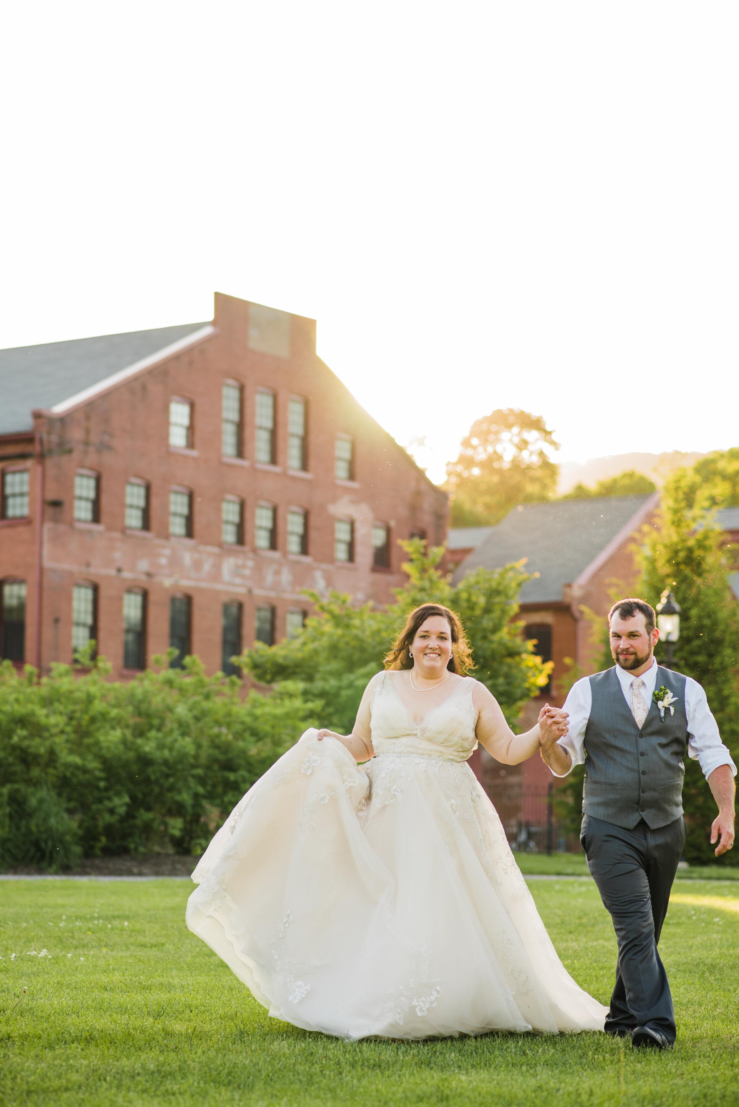 Wedding couple walking through a field at golden hour.