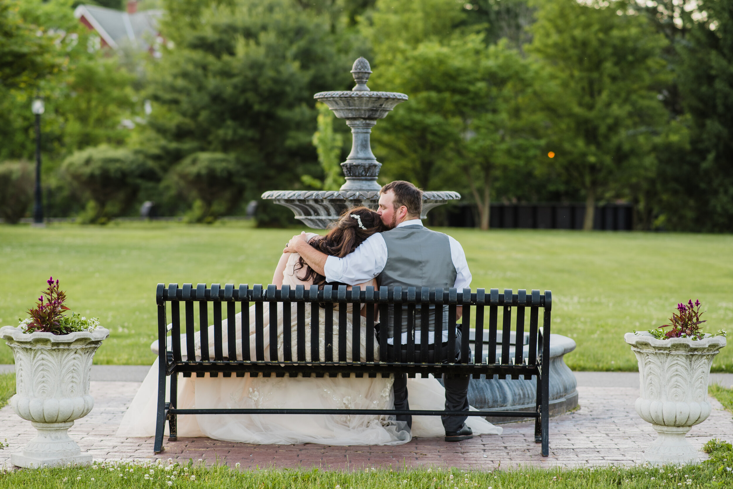 Wedding couple kissing on a bench by a fountain.