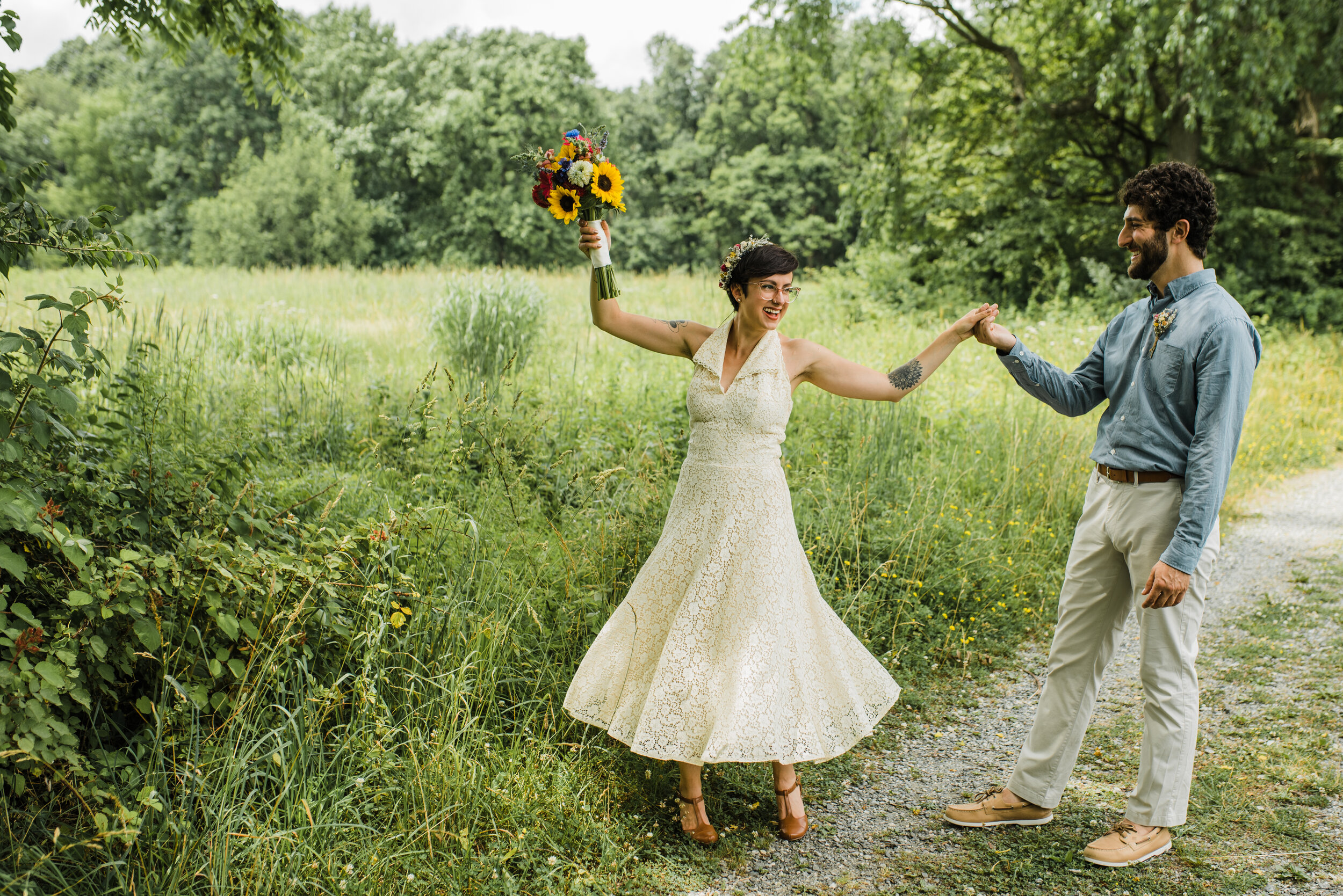 Wedding couple dancing in a field. Bride wears a vintage dress and flower crown.