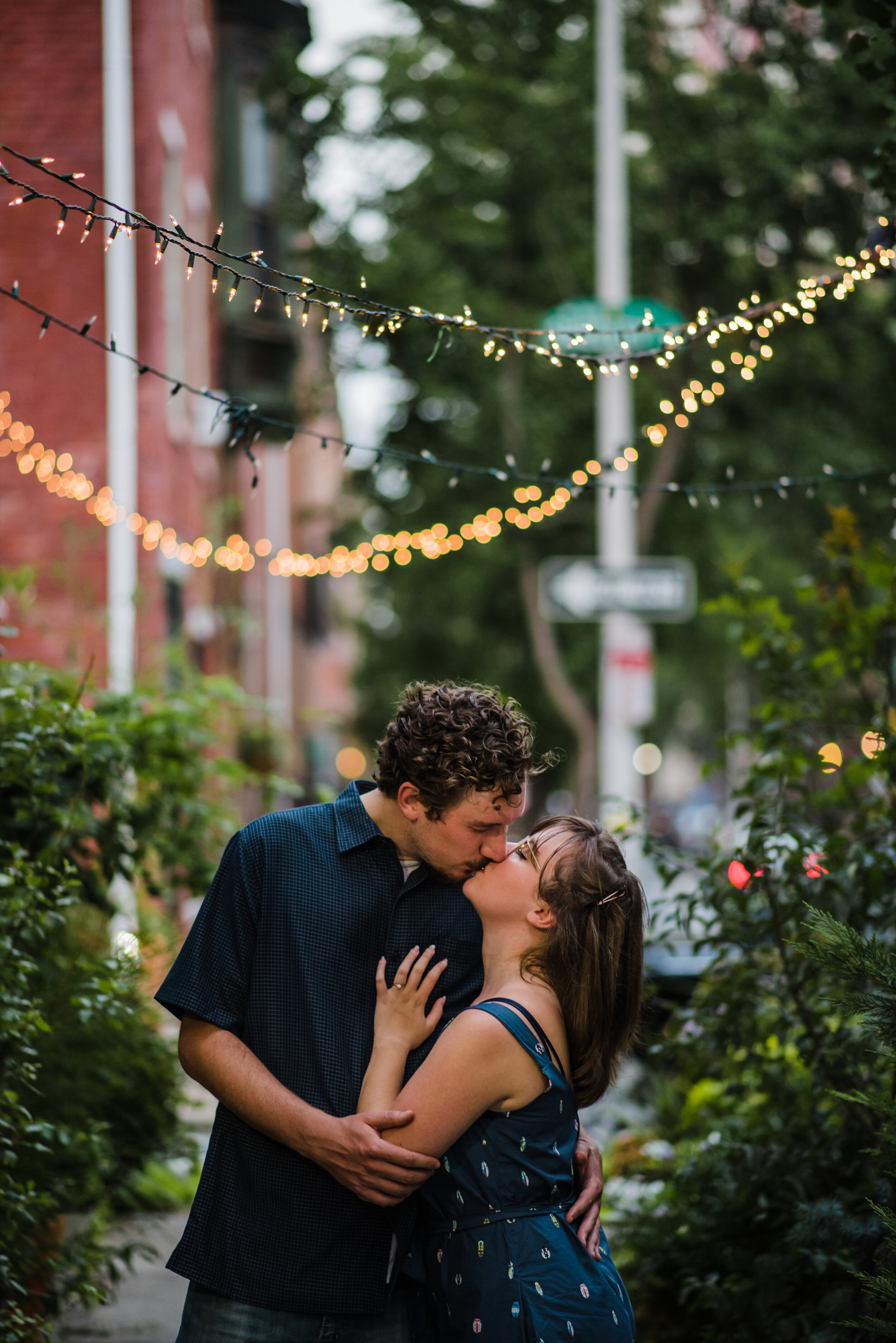 Philly engagement photography on a center city street under string lights.