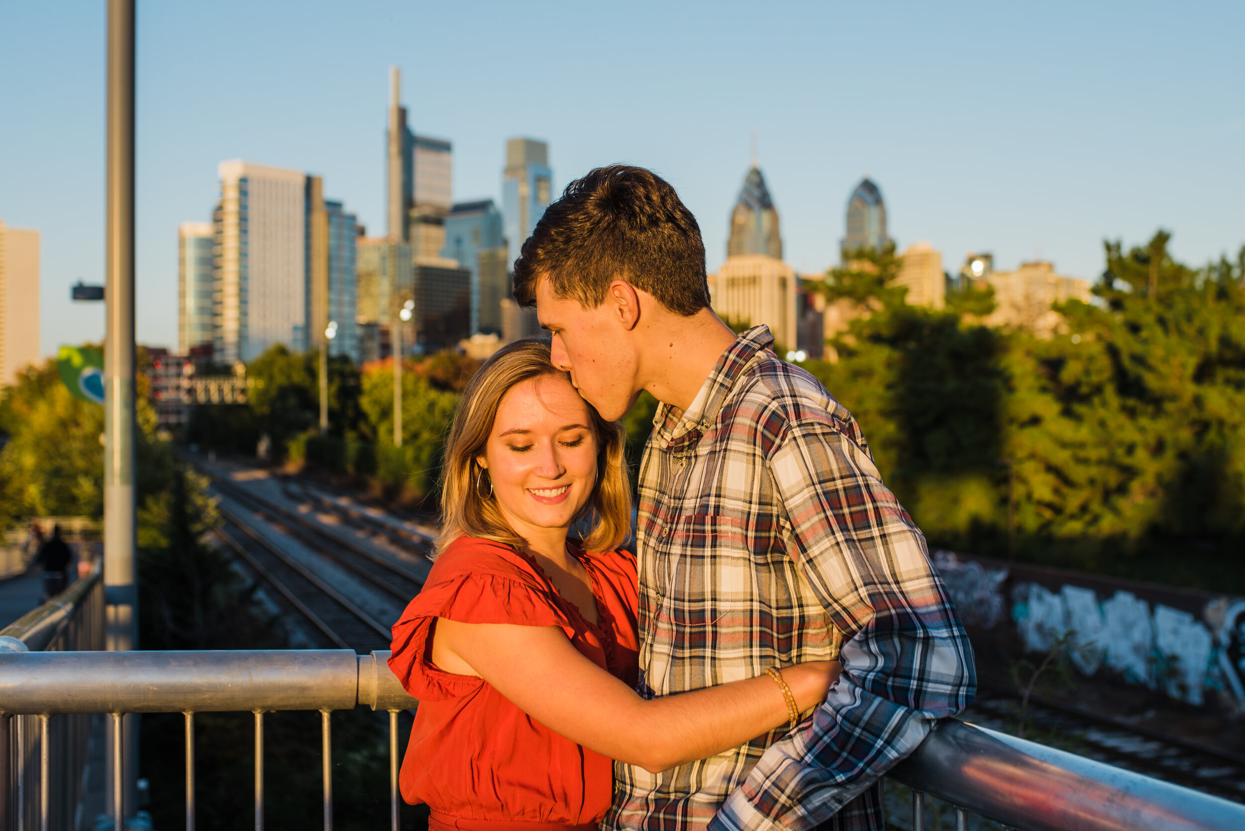 Philly couple kissing with the skyline behind them for their engagement photos
