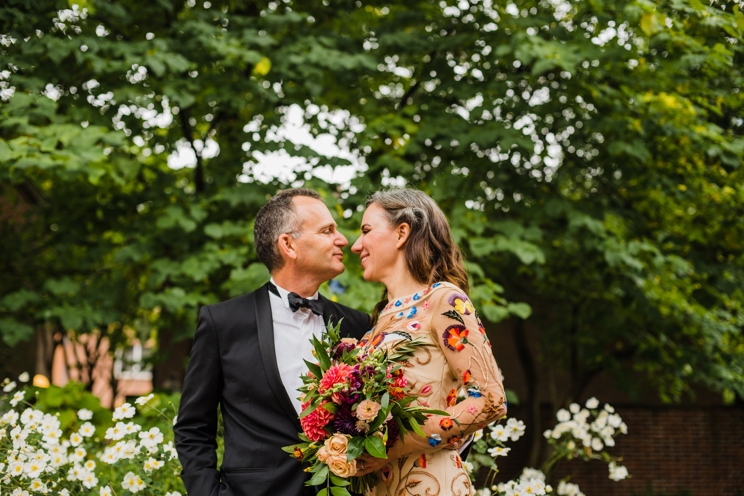 Wedding couple with the bride in a colorful dress surrounded by greenery.