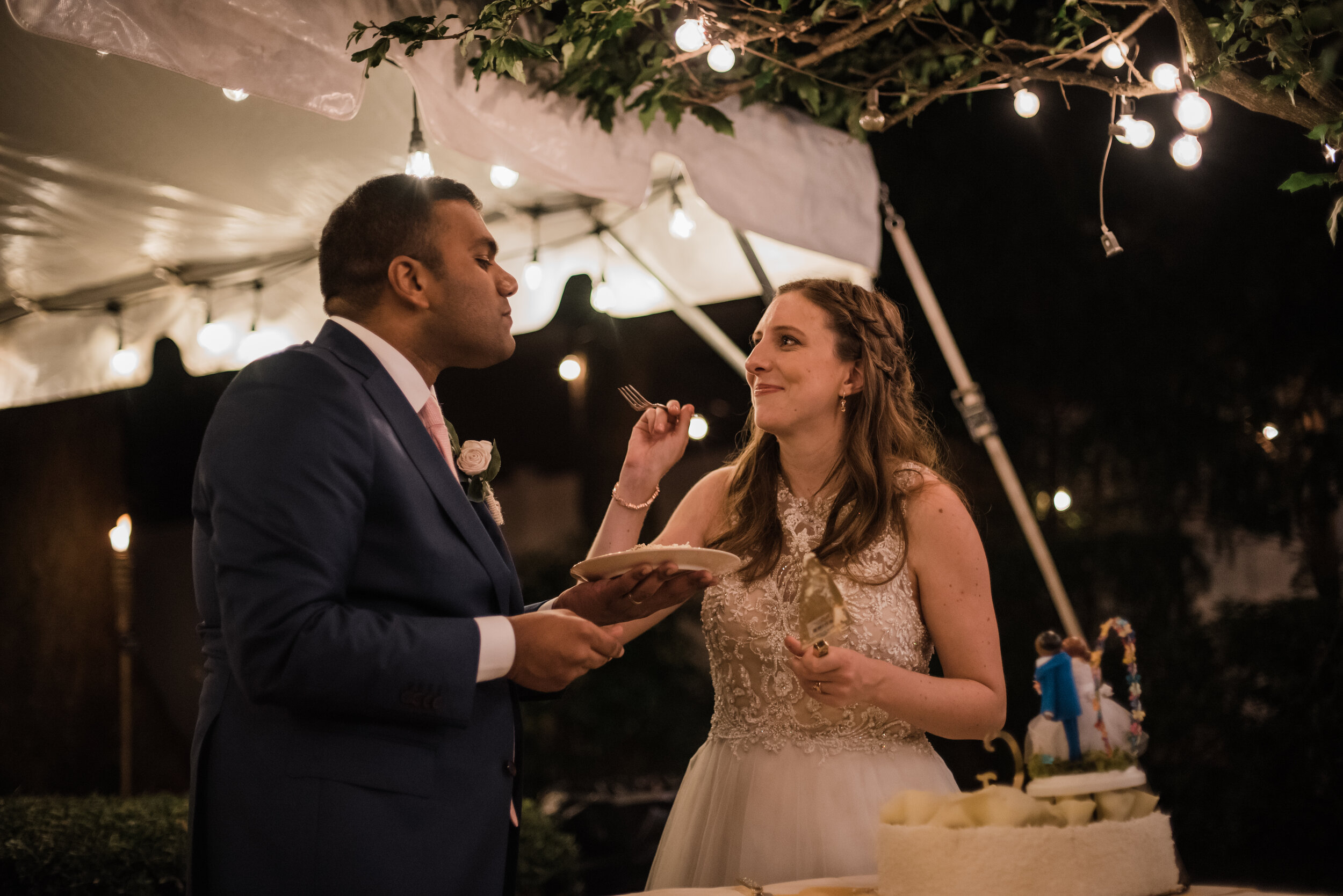 Wedding couple feeding each other cake.