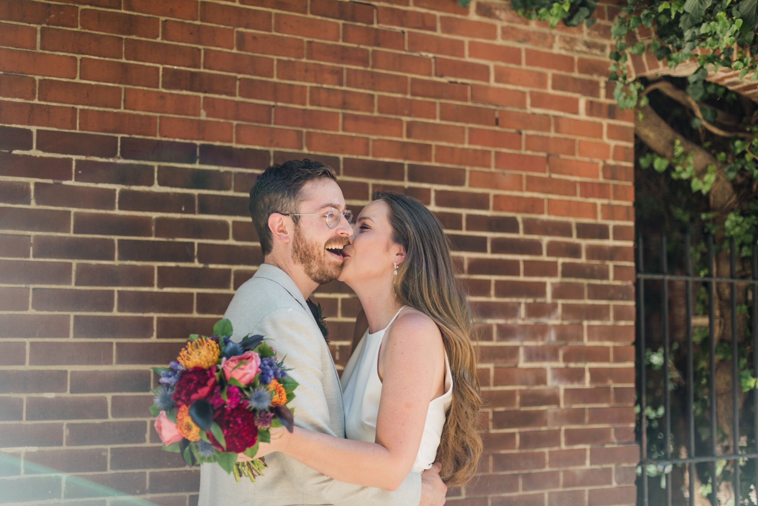 Wedding couple kissing by a brick wall with a colorful bouquet of flowers.