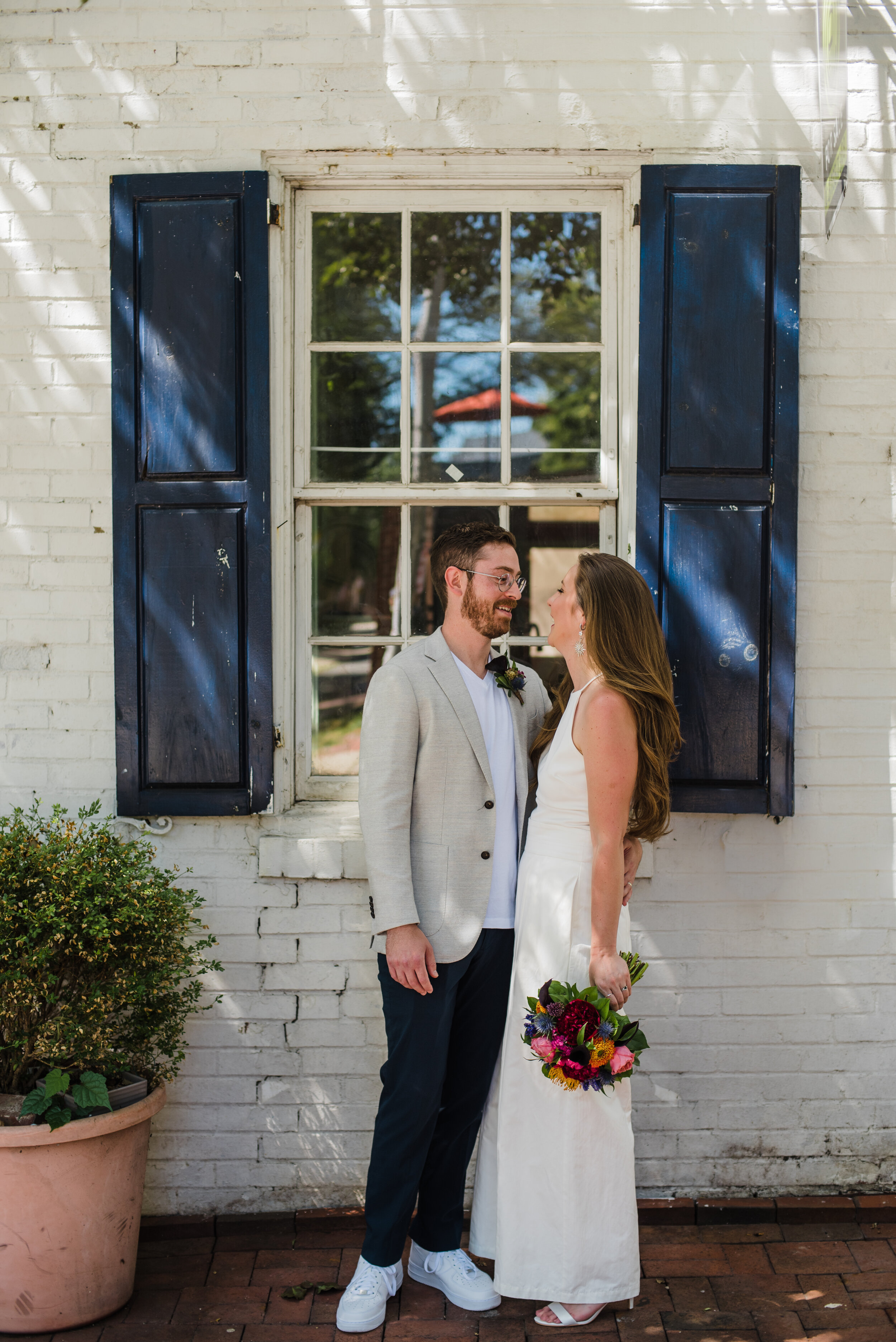 Wedding couple in front of a classic Philly home with blue shutters. The bride is wearing a white jumpsuit.