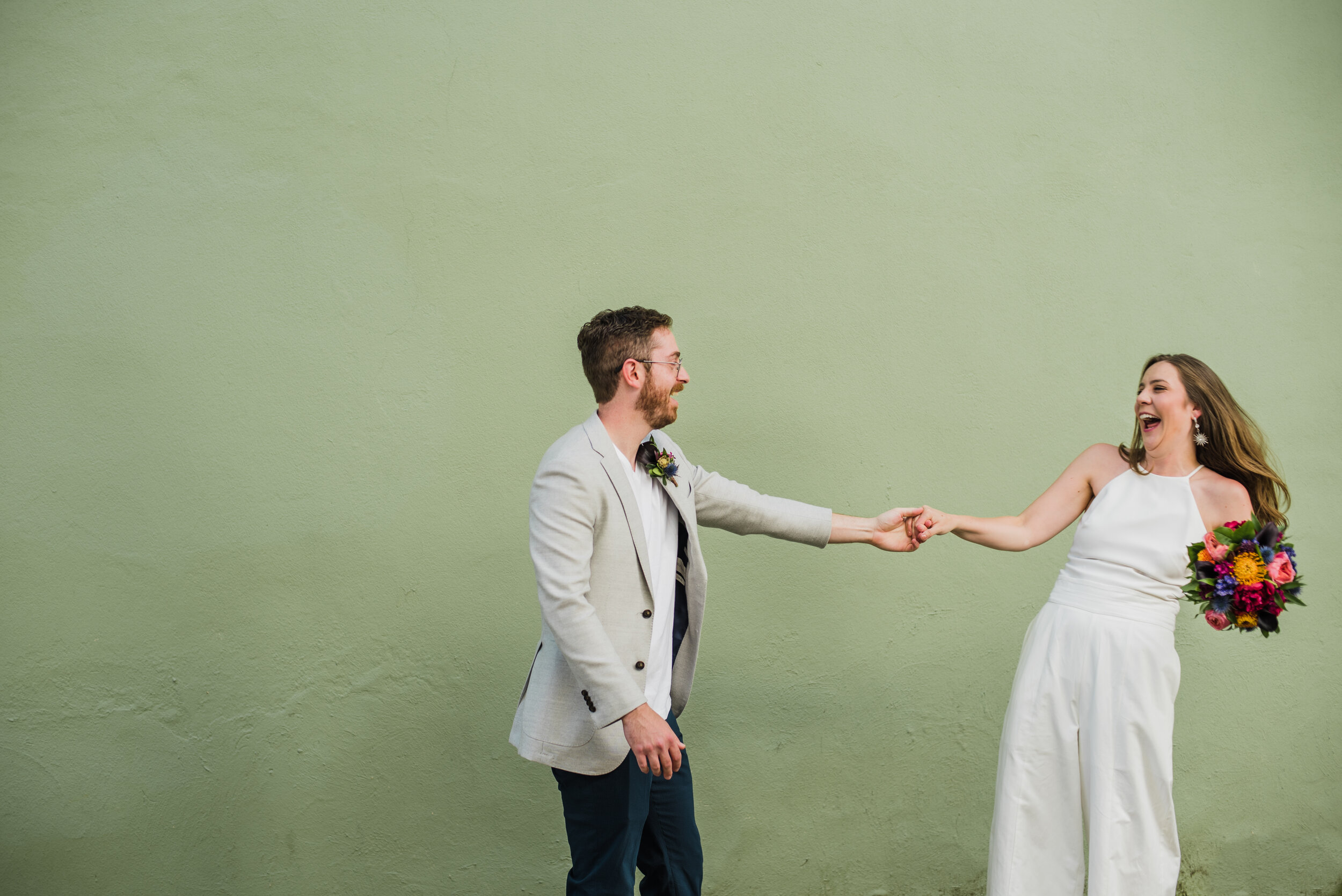 Wedding couple dancing in front of a pale green wall.