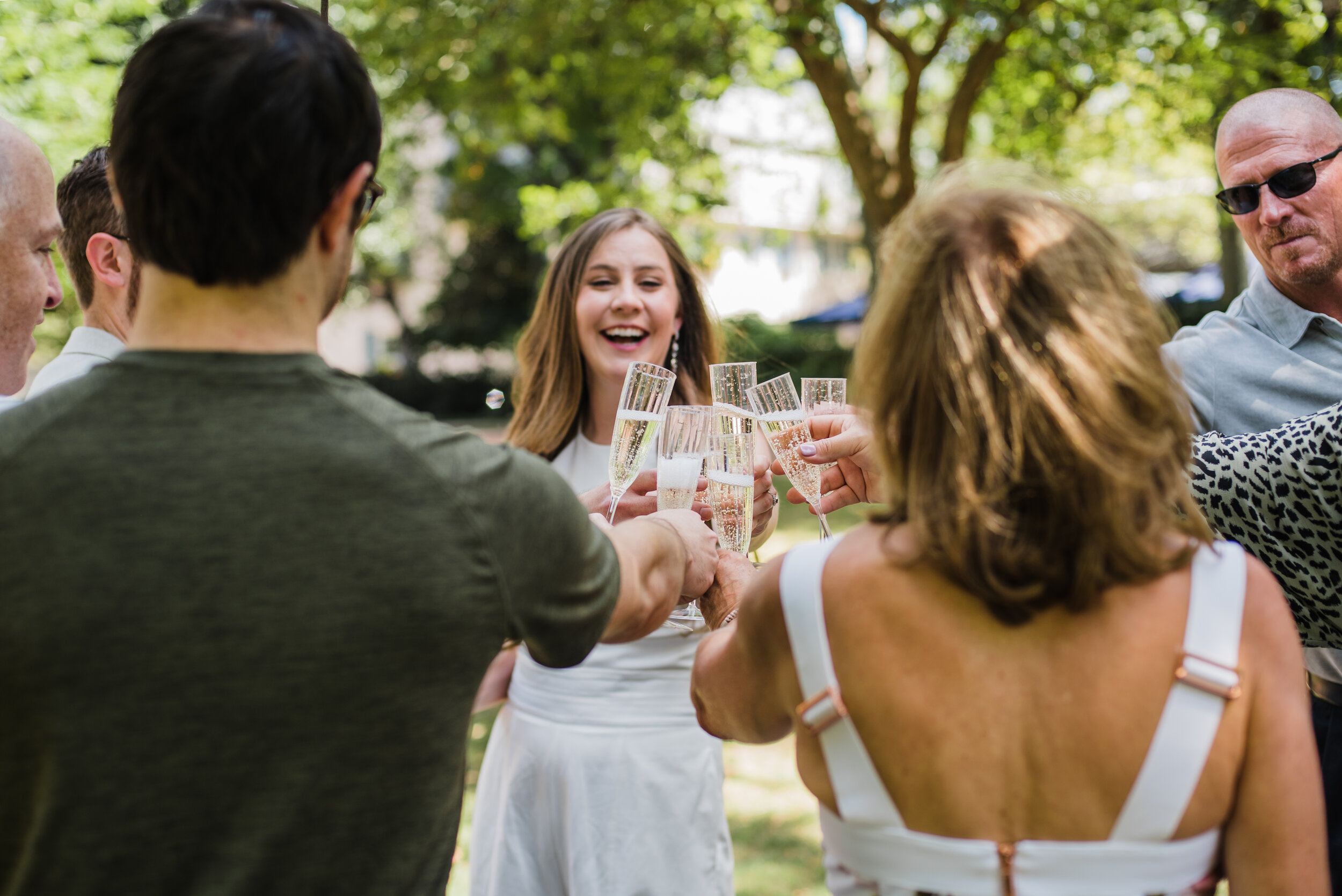 Small group of elopement guests celebrating with champagne.