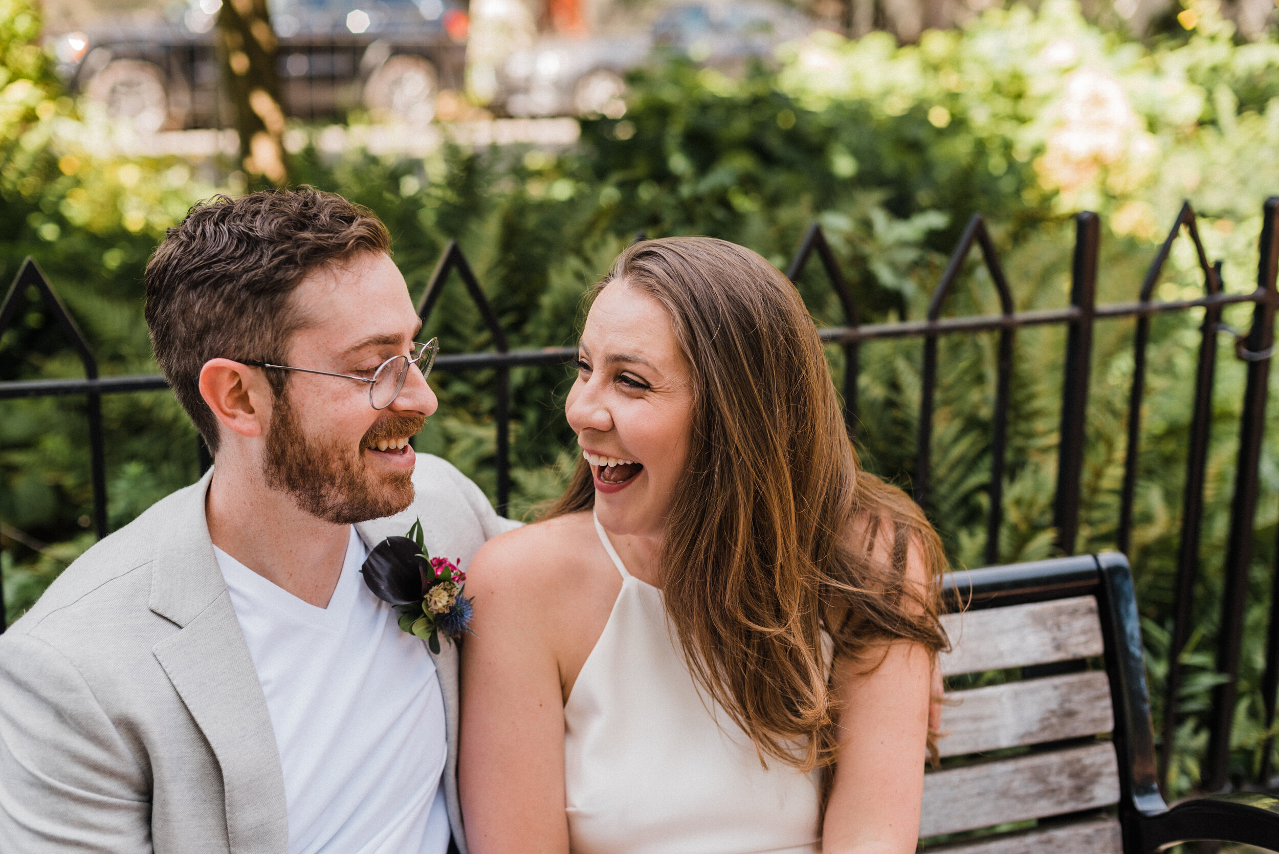 Wedding couple laughing together on a park bench after their outdoor elopement.