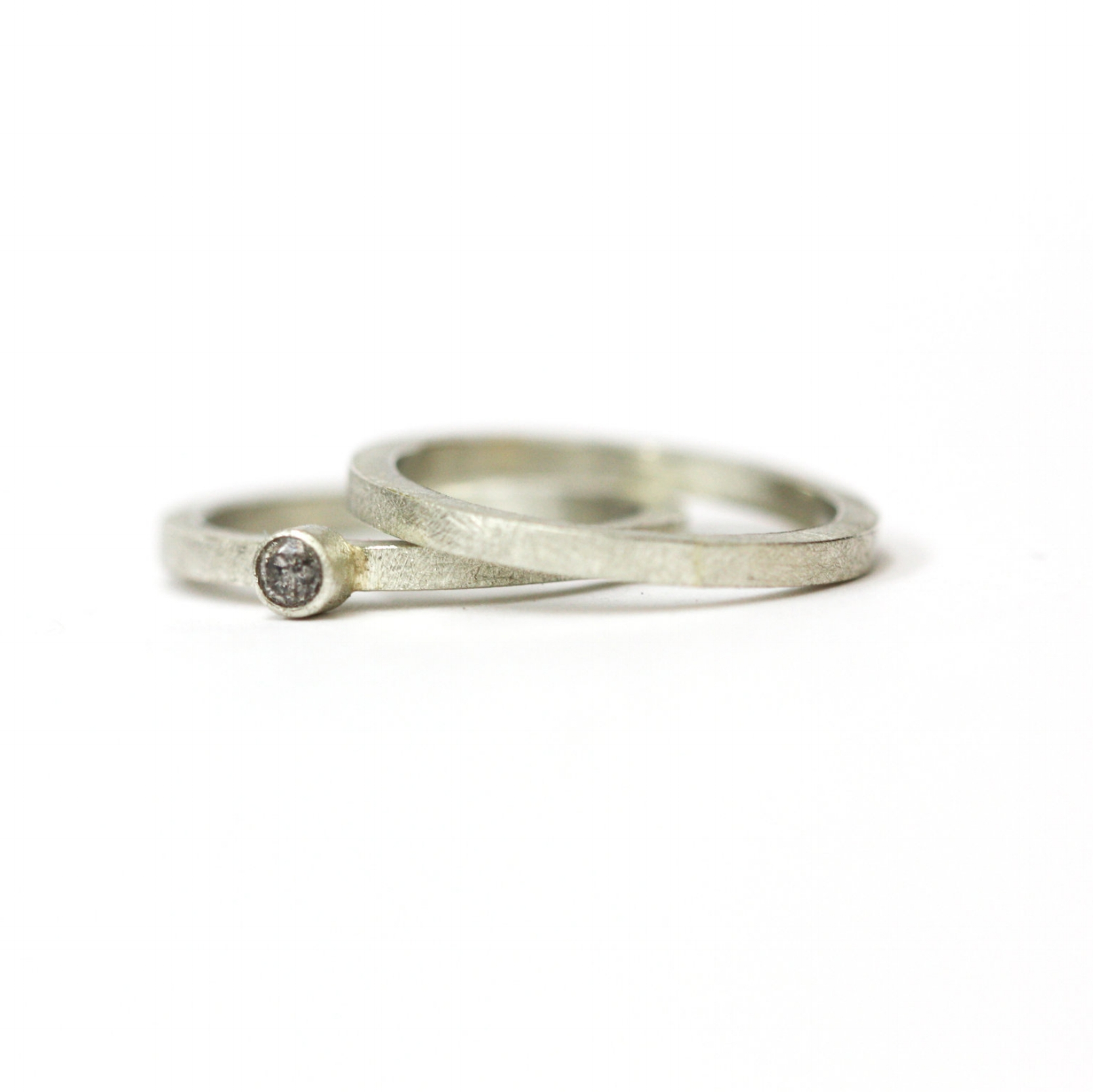 Wedding & Engagement Sets  This pair of rings is made from 9ct White gold with a simple speckled grey diamond set centrally on one of the bands.